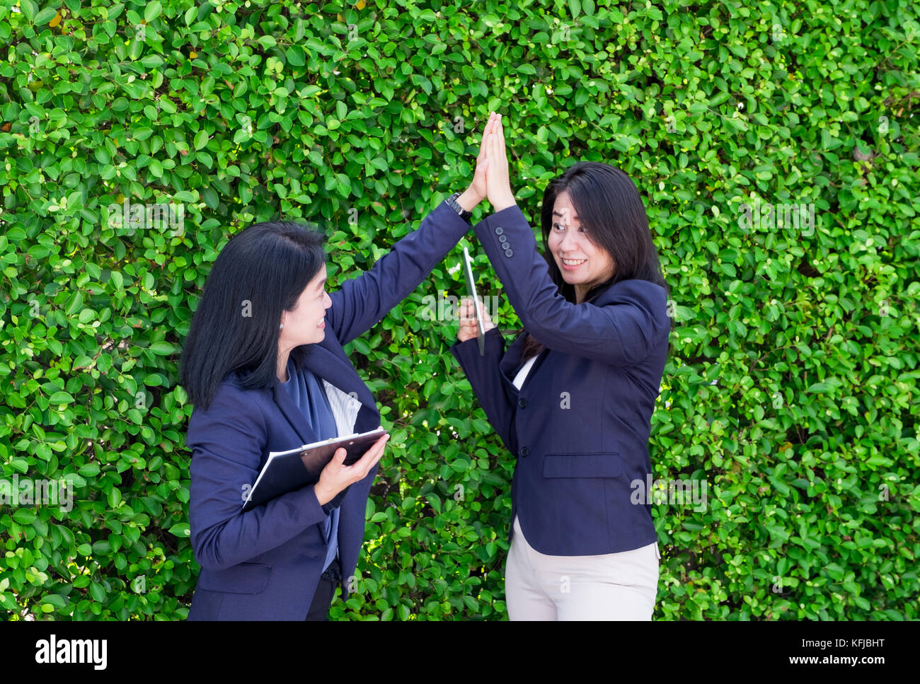 Dos países asiáticos empresaria alta cinco para el éxito empresarial fuera de oficina en hojas verdes,el Imagen De Stock