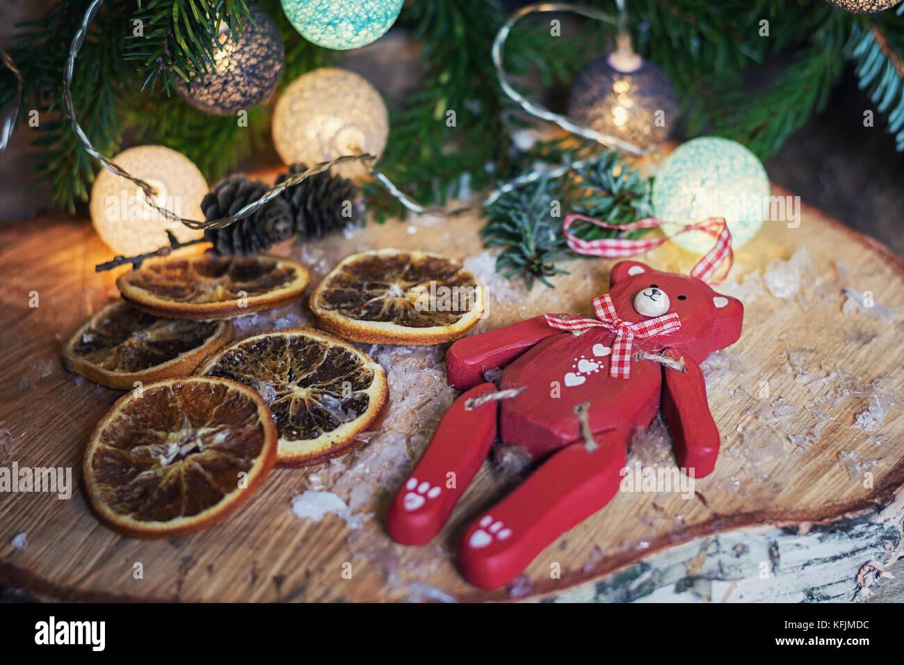 Oso de madera roja tumbado sobre un disco de madera de abedul delante de una sucursal de navidad decorado con bolas de Navidad iluminado Foto de stock
