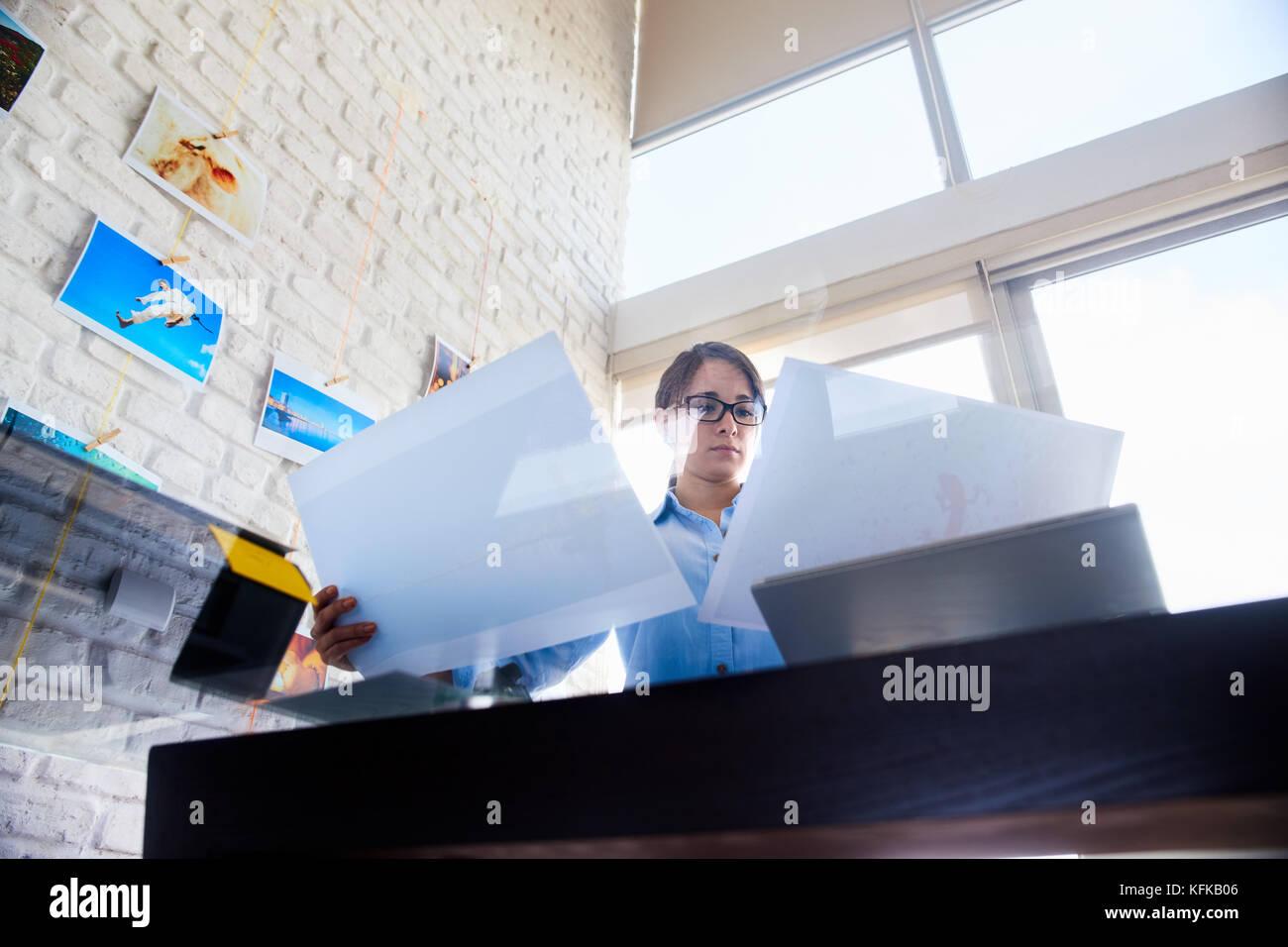 Joven y pequeña empresa. ocupada mujer trabajando como fotógrafo en studio. chica hispana control de imágenes Imagen De Stock