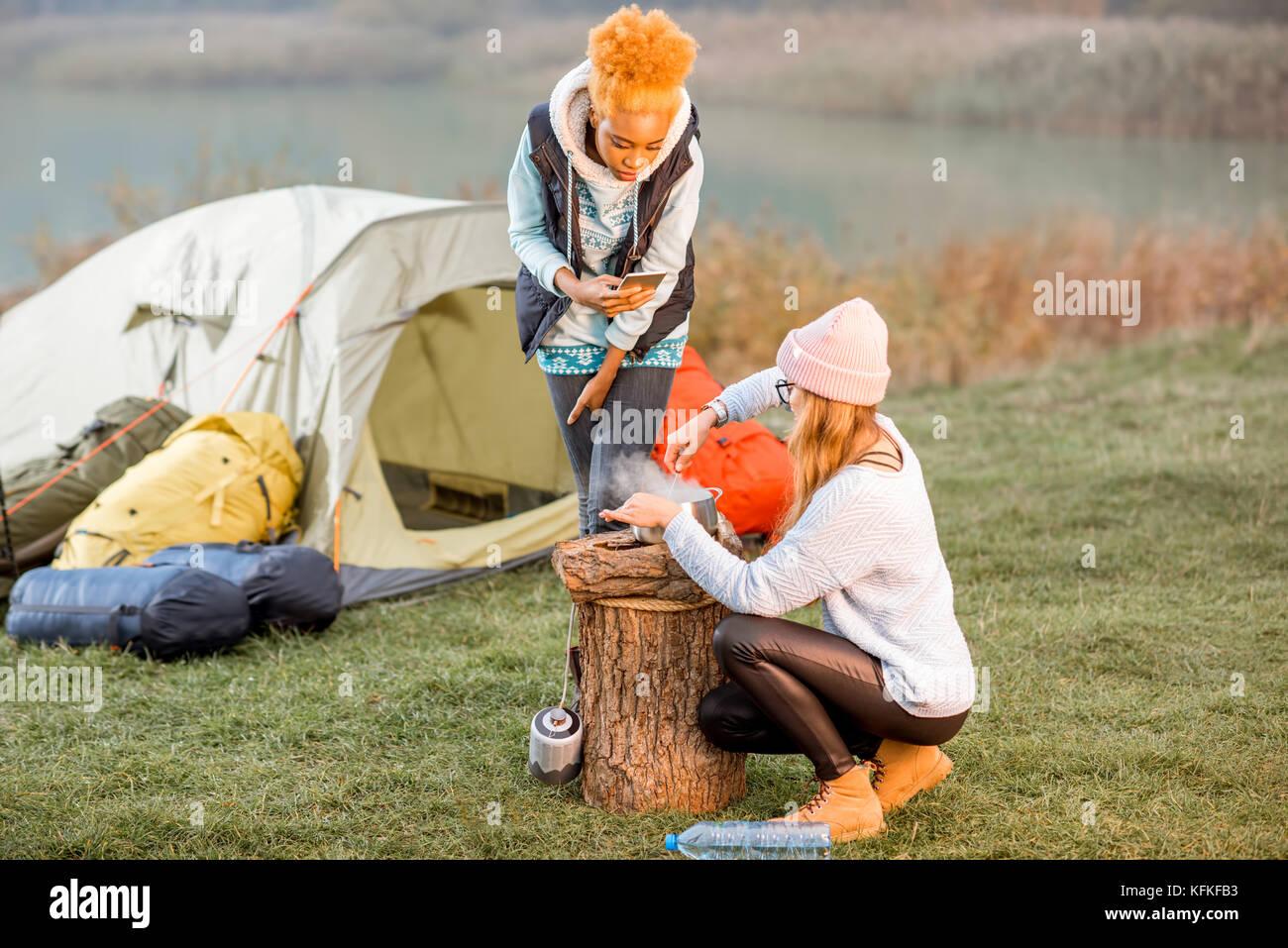 La mujer cocinando comida en el camping Foto de stock