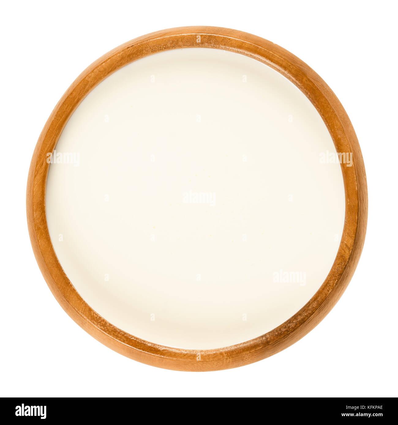 Crema dulce fresco en el tazón de madera un producto lácteo compuesto de la capa de materia grasa butírica Imagen De Stock
