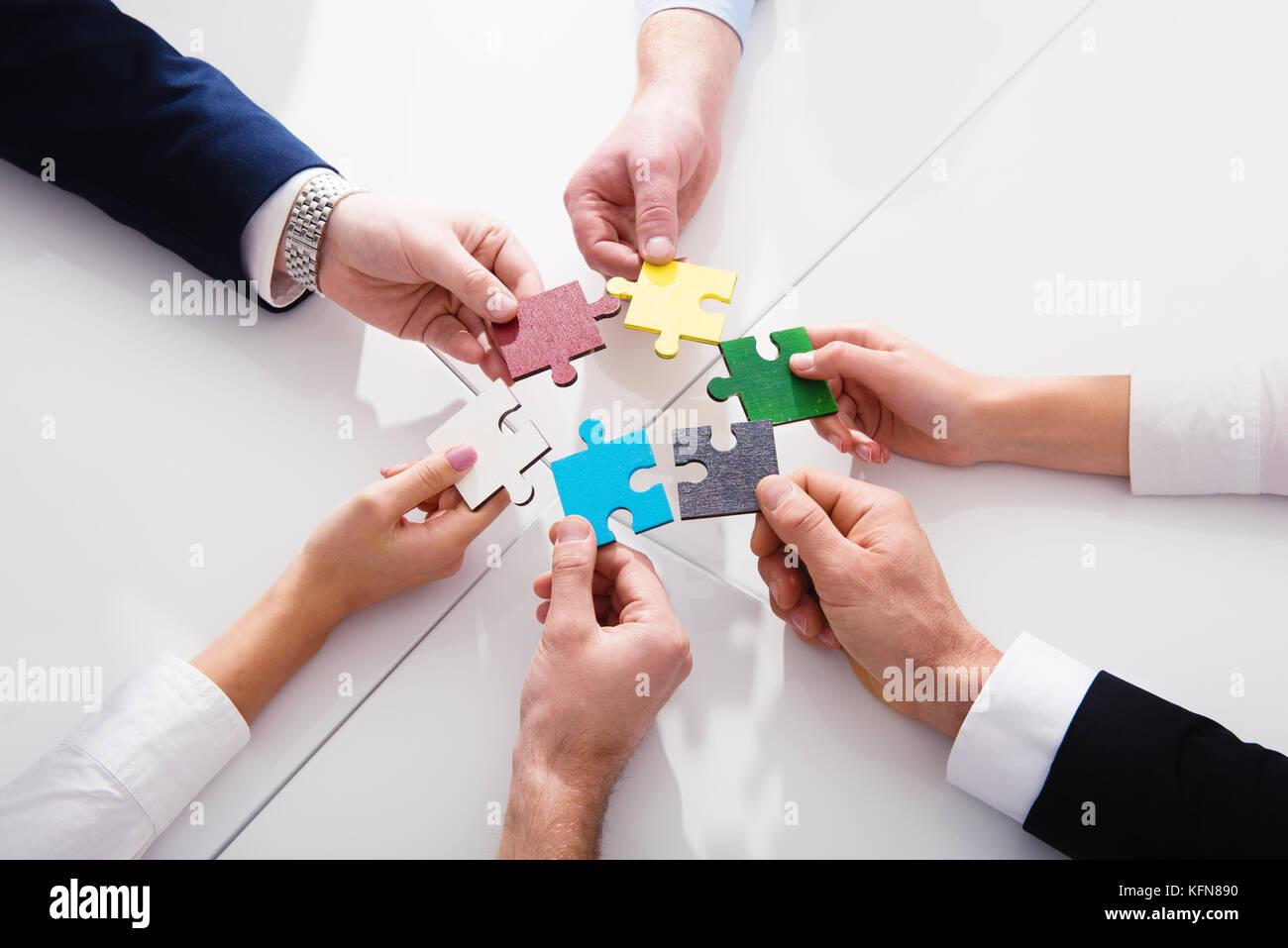 Trabajo en equipo de socios. Concepto de integración y arranque con piezas de rompecabezas Imagen De Stock