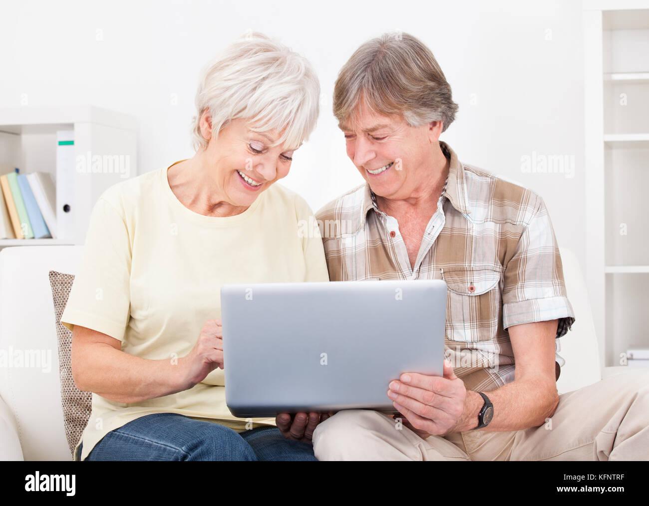 Retrato de la feliz pareja senior sentado en sofá con ordenador portátil Foto de stock