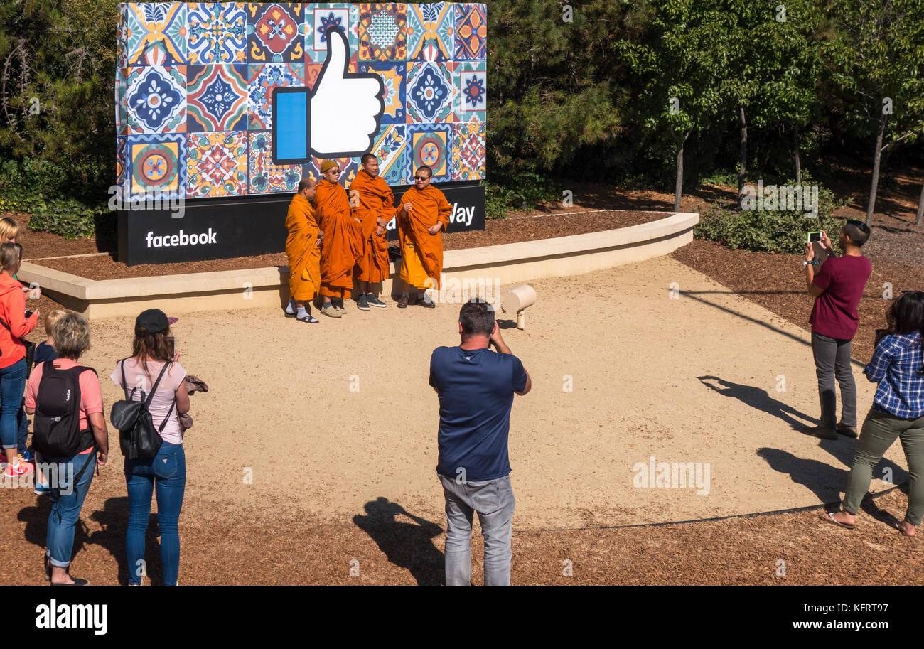 Facebook HeadquartersThumbs hasta firmar con monjes budistas y otros turistas tomando fotos a la entrada a 1 Hacker Imagen De Stock