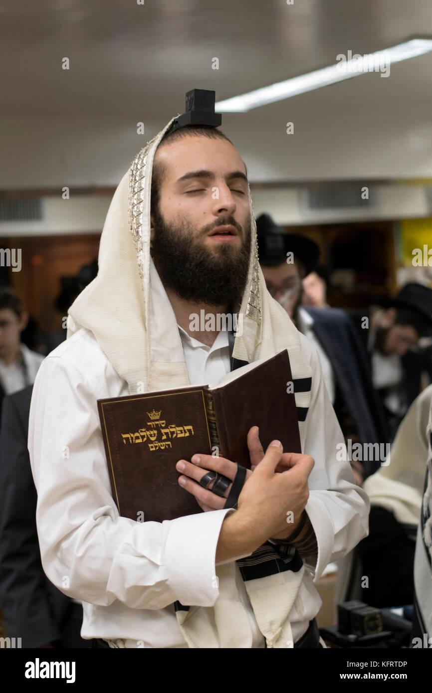 Un hombre judío ortodoxo en oración reflexiva en una sinagoga en Crown Heights, Brooklyn, Nueva York. Imagen De Stock