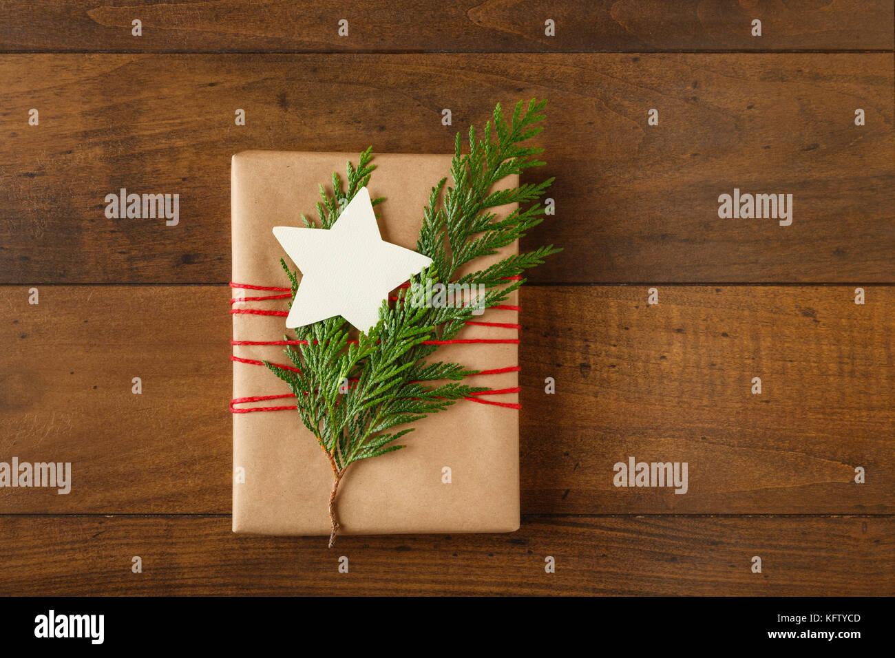 Regalo de navidad envuelto en papel de embalaje reciclados con decoraciones y siempreverdes naturales una virgen, Imagen De Stock