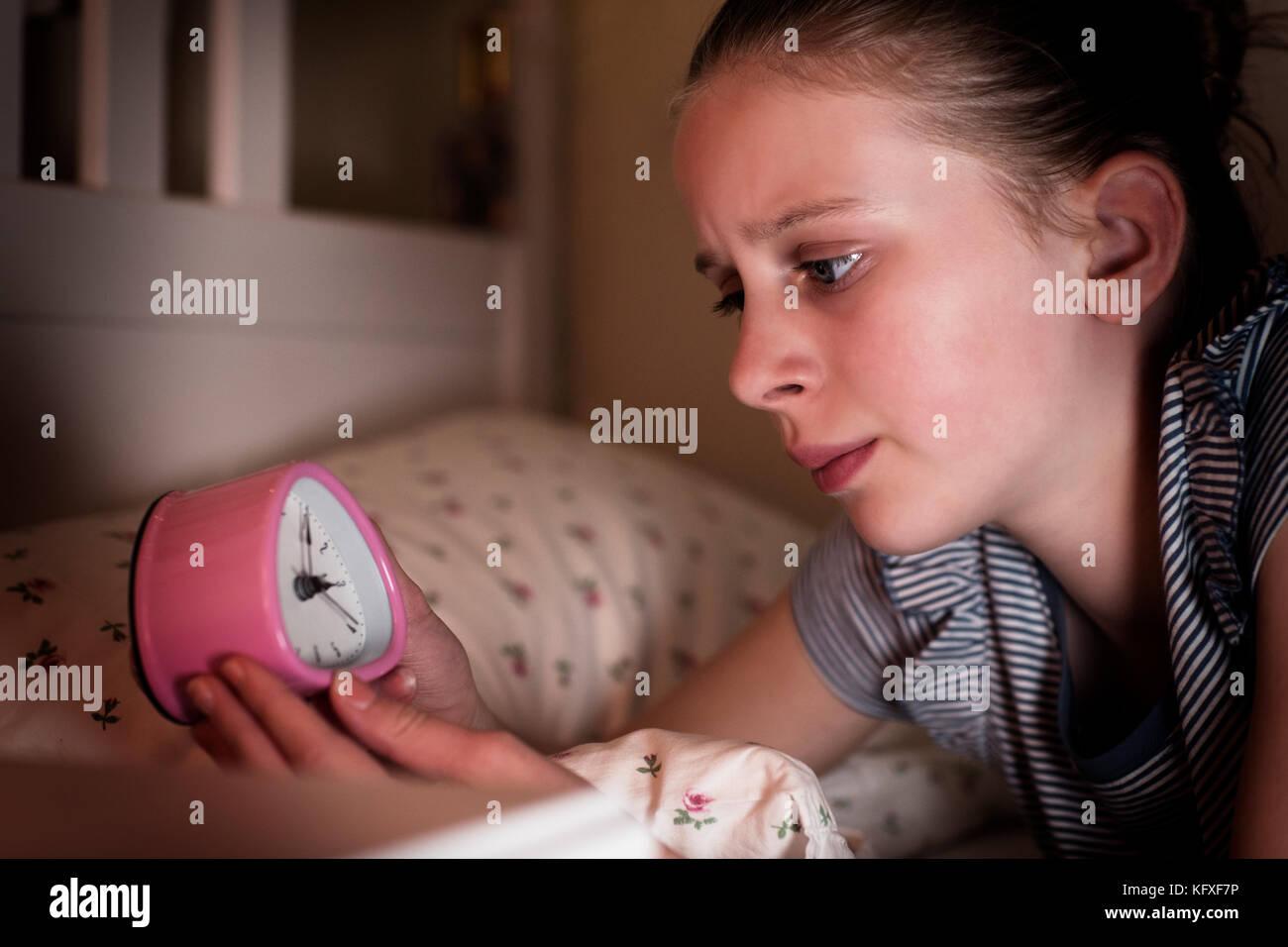 Ansioso chica incapaz de dormir por la noche mirando el reloj Foto de stock