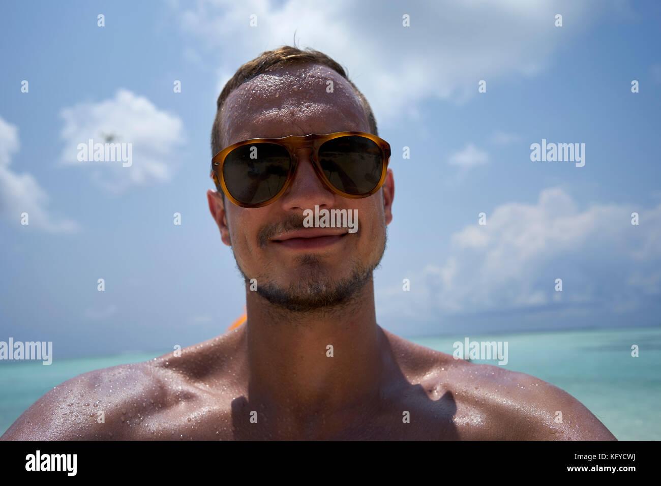 Hombre con pelo corto, barba y gafas de sol toma un selfie en la playa Imagen De Stock