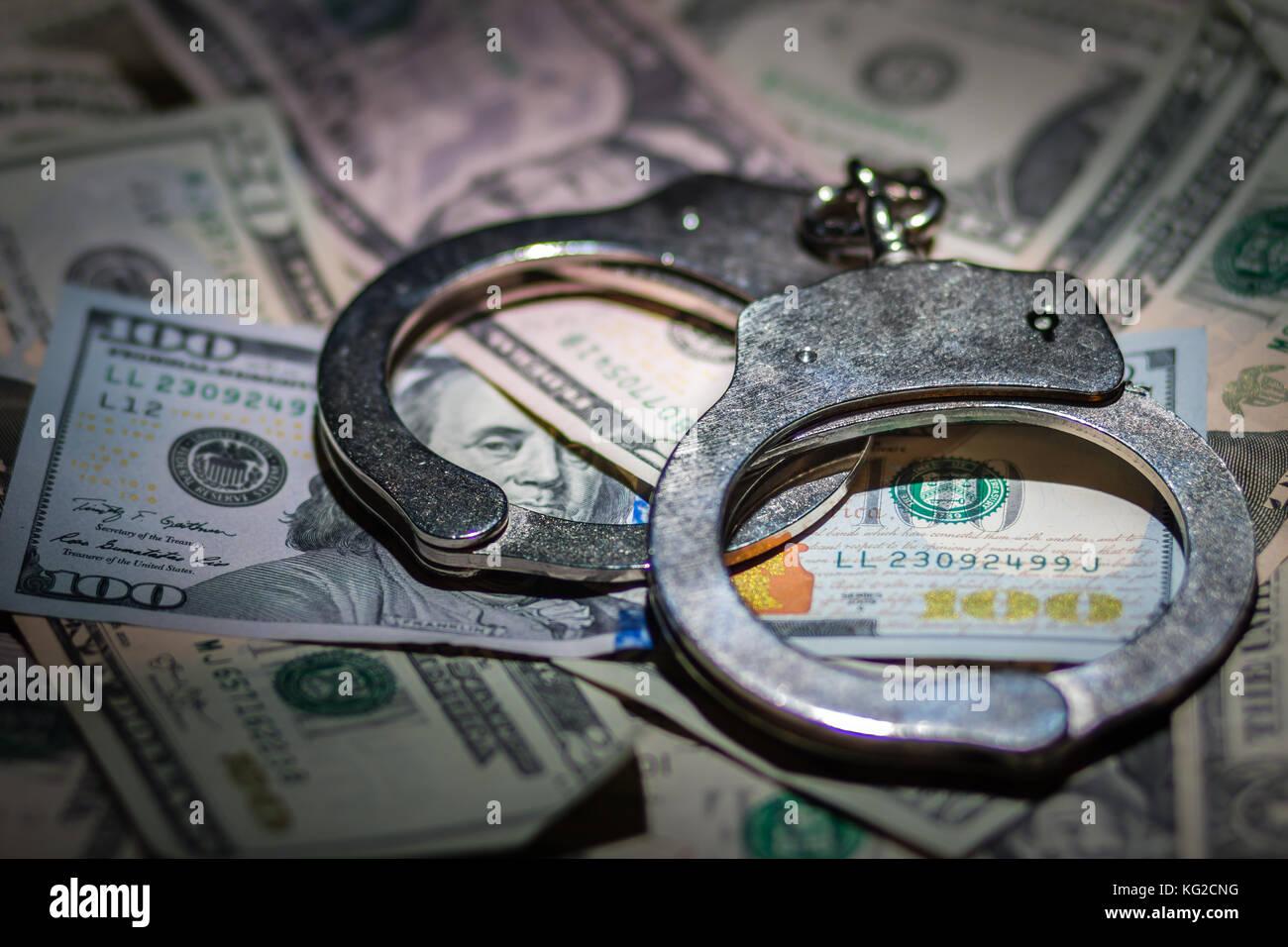 Un par de esposas cerrado sobre un montón de Dólares americanos Imagen De Stock