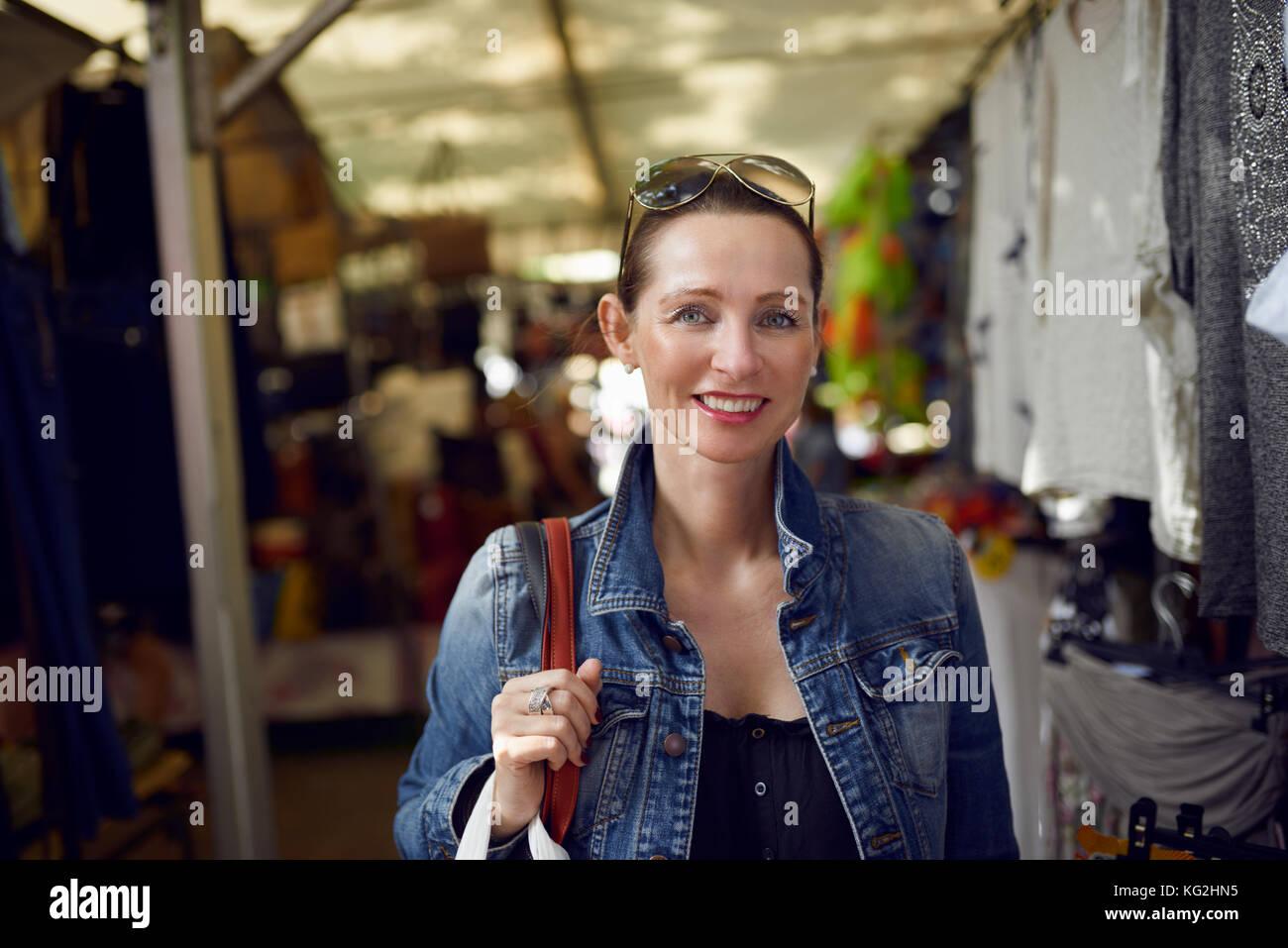 Feliz atractiva mujer elegante de compras en un mercado al aire libre de pie mirando a la cámara con una amplia Imagen De Stock