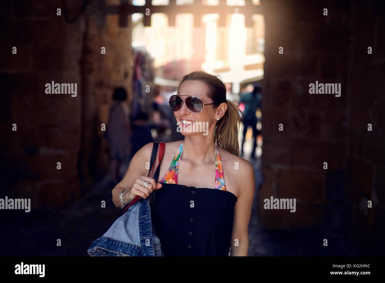 Moda atractiva mujer con gafas de sol y llevar un gran bolso sobre su hombro de compras en la ciudad mirando hacia Imagen De Stock
