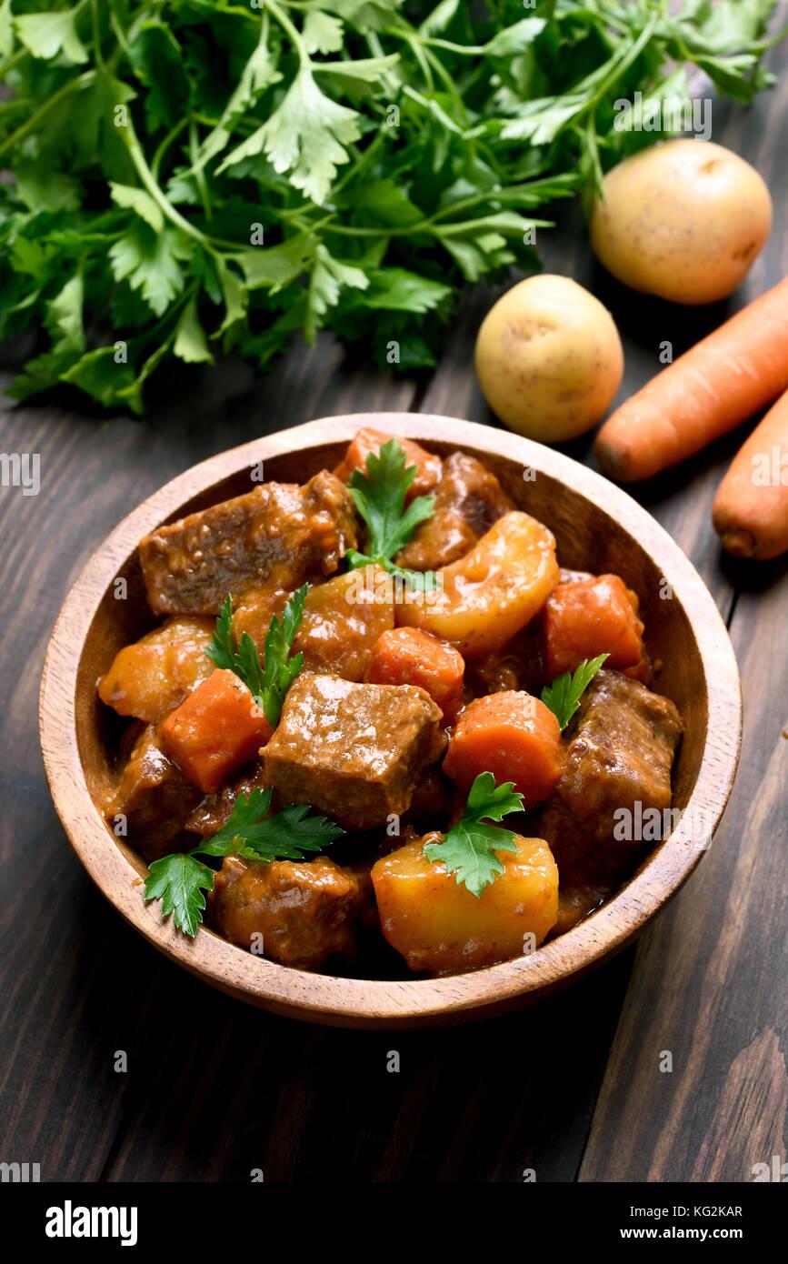 Goulash, estofado de carne con verduras en el recipiente sobre la mesa de madera Imagen De Stock