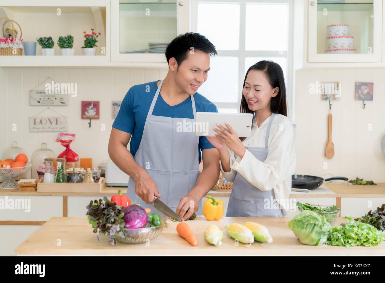 Joven y bella asiática el esposo y la esposa buscando receta de menú en digital tablet en la cocina en Imagen De Stock