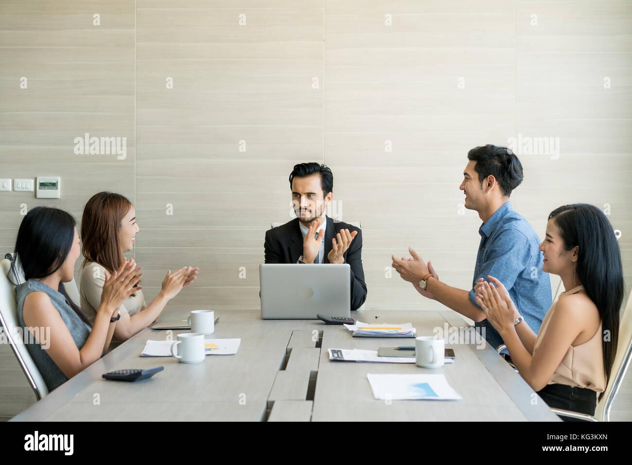 Manos de socios comerciales aplaudiendo al periodista después de escuchar su presentación en reunión. Foto de stock