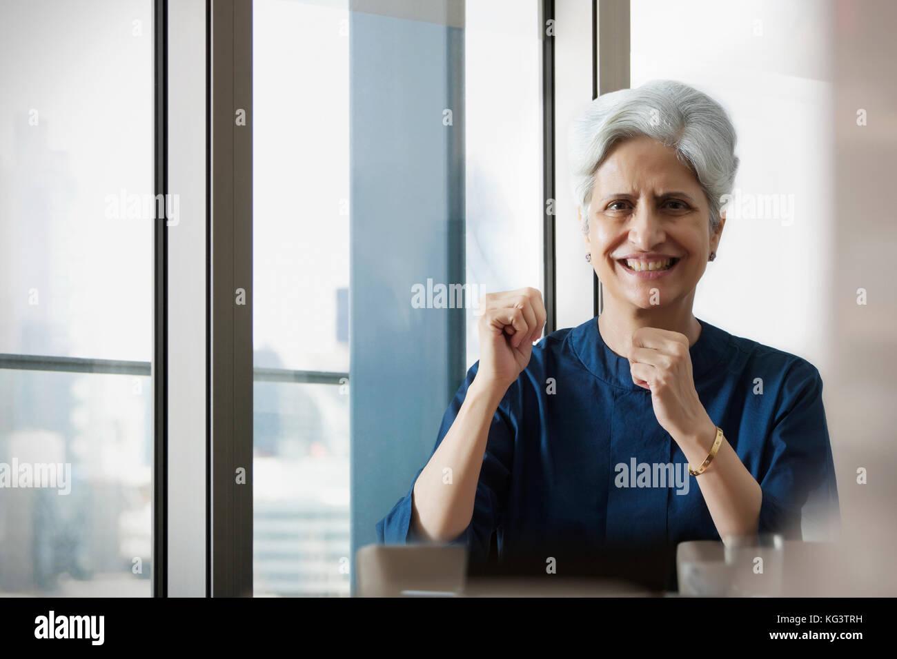 Mujer sonriente vítores con puños de mano Imagen De Stock