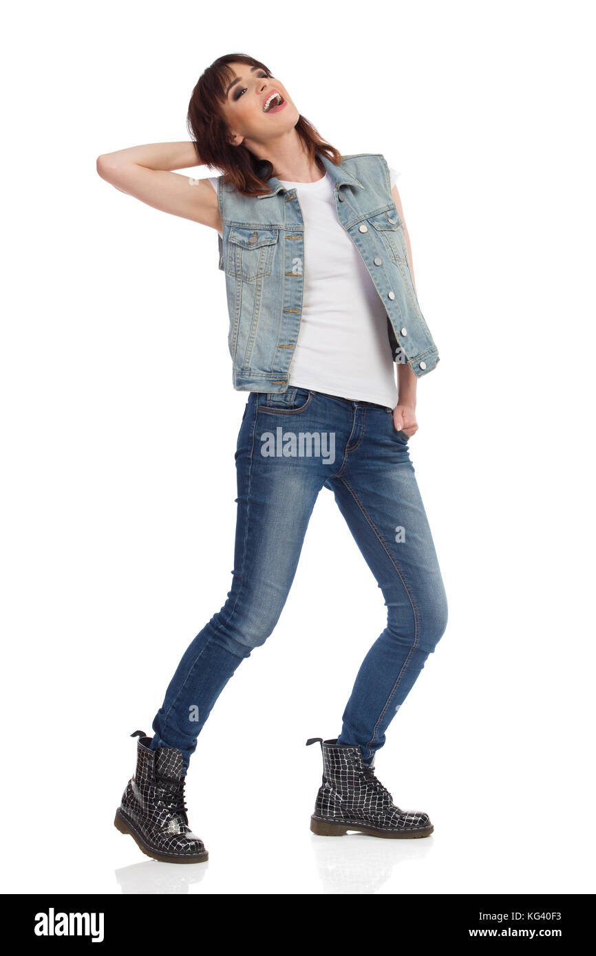 Mujer joven en jeans chaleco y botas de negro está de pie, piernas separadas, mirando a otro lado y riendo. Imagen De Stock