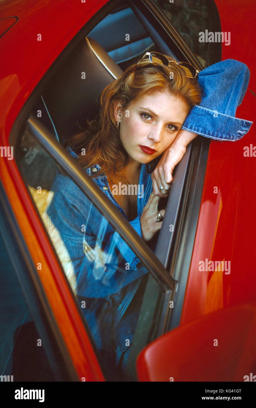 Mujer joven mirando desde la ventana de coche. Imagen De Stock