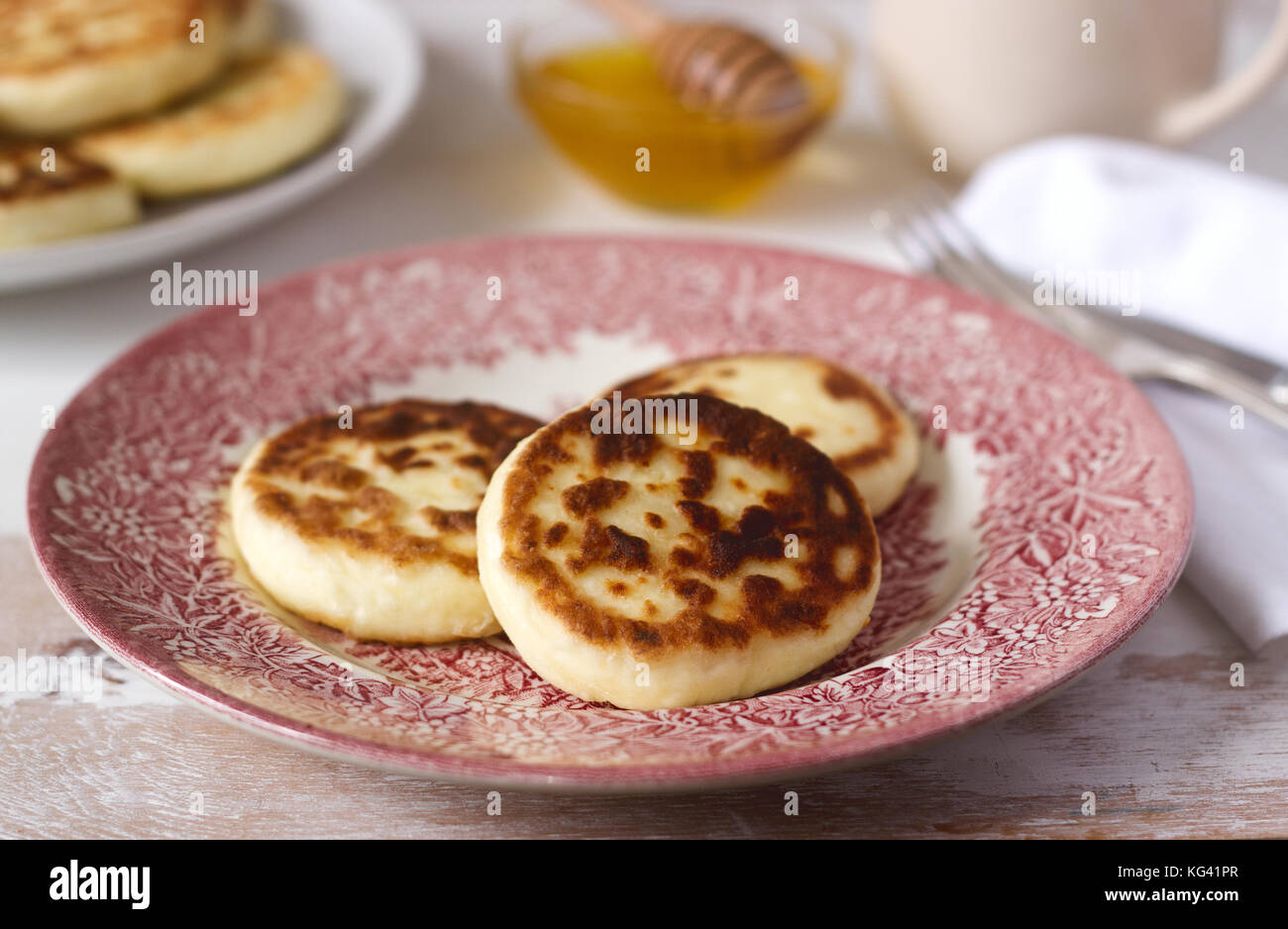 Requesón tortitas, syrniki caseros con miel y crema agria. Foto de stock