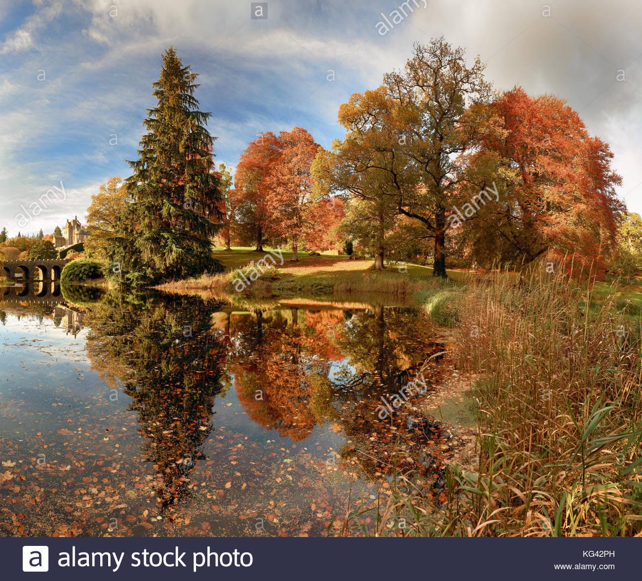 Árbol del otoño y el puente reflexiones de un estanque en Drummond Castle Gardens. Crieff, Perth y Kinross. Foto de stock