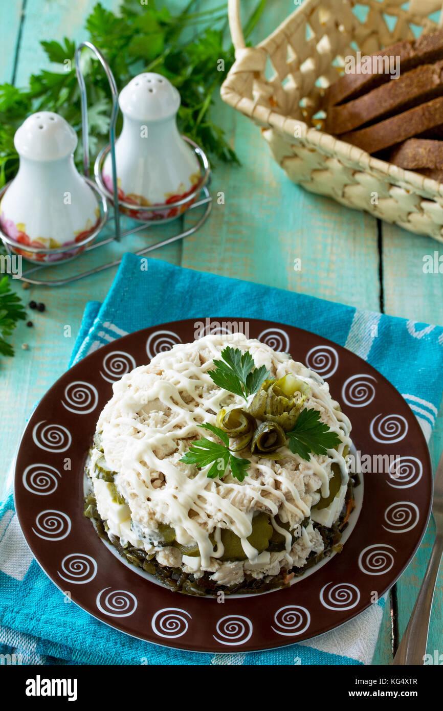 Home un bocadillo en la mesa de madera. Cocina con ensalada de pollo, arroz y el repollo de mar. Imagen De Stock