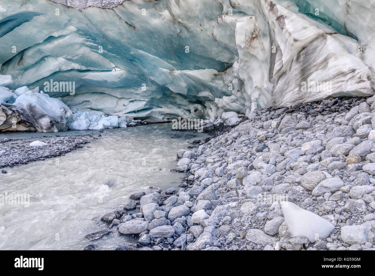 Una colorida vista de la cueva de hielo en el glaciar y el origen del rápido río de montaña que fluye Imagen De Stock