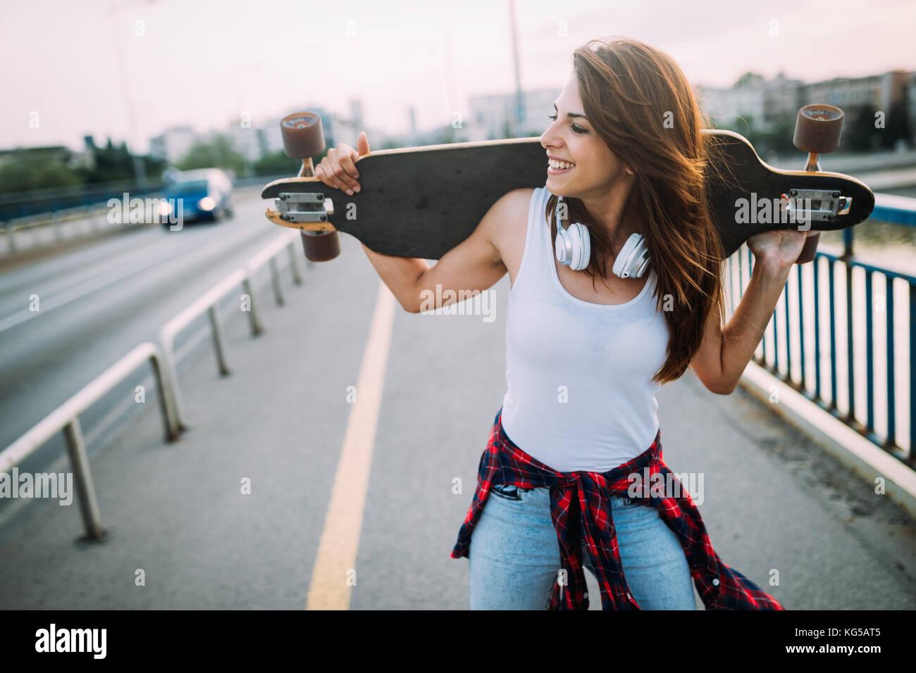Retrato de hermosa niña sonriente llevando skateboard Imagen De Stock