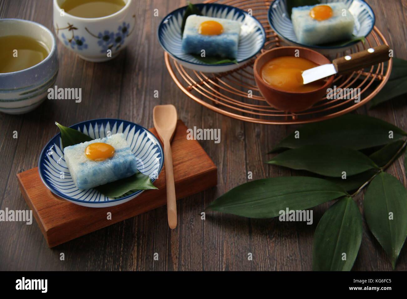 Pulut tai tai o pulut tekan, peranakan blanco y azul pastel de arroz glutinoso con kaya jam Imagen De Stock