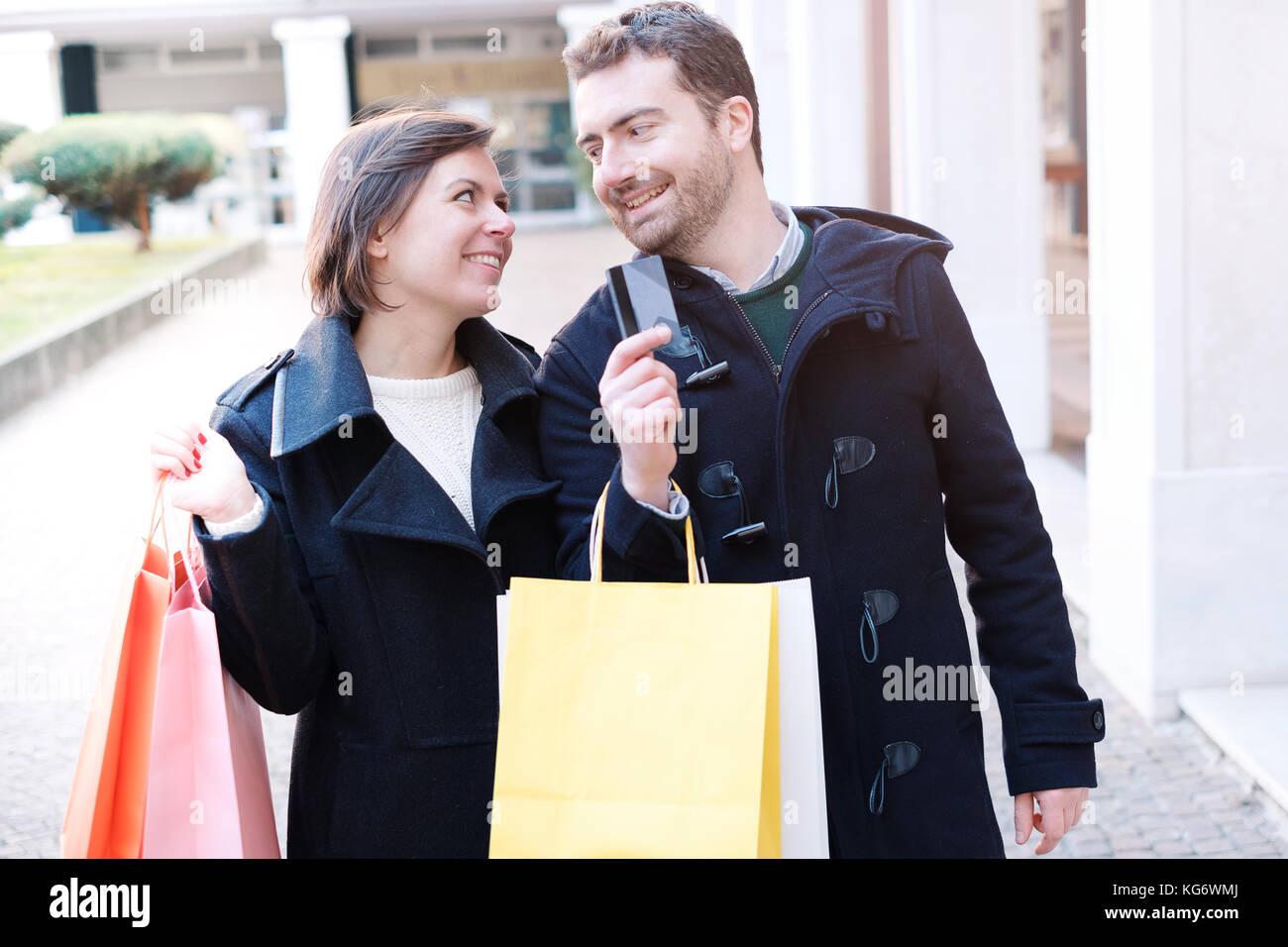 Hombre sujetando un tarjeta de crédito preparada para el tiempo de compras con su novia Imagen De Stock