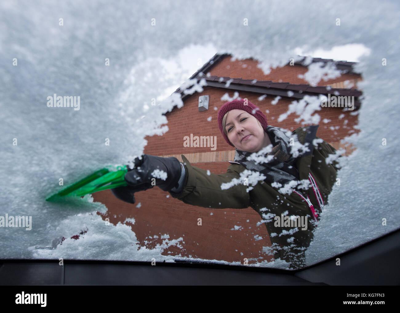 Mujer raspa hielo de car window Imagen De Stock