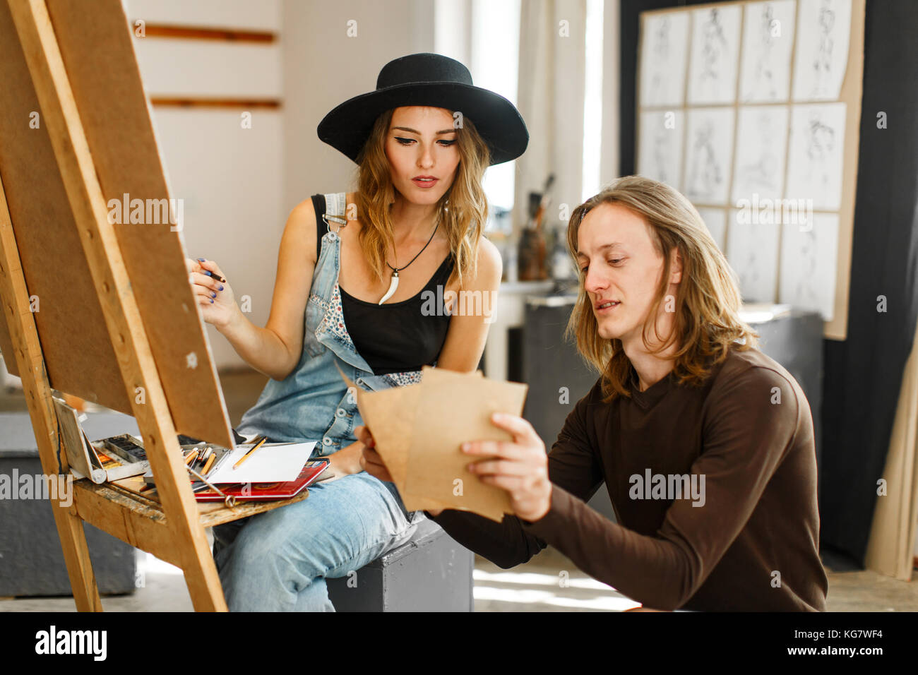 Artista consultar a su colega mientras dibuja Imagen De Stock