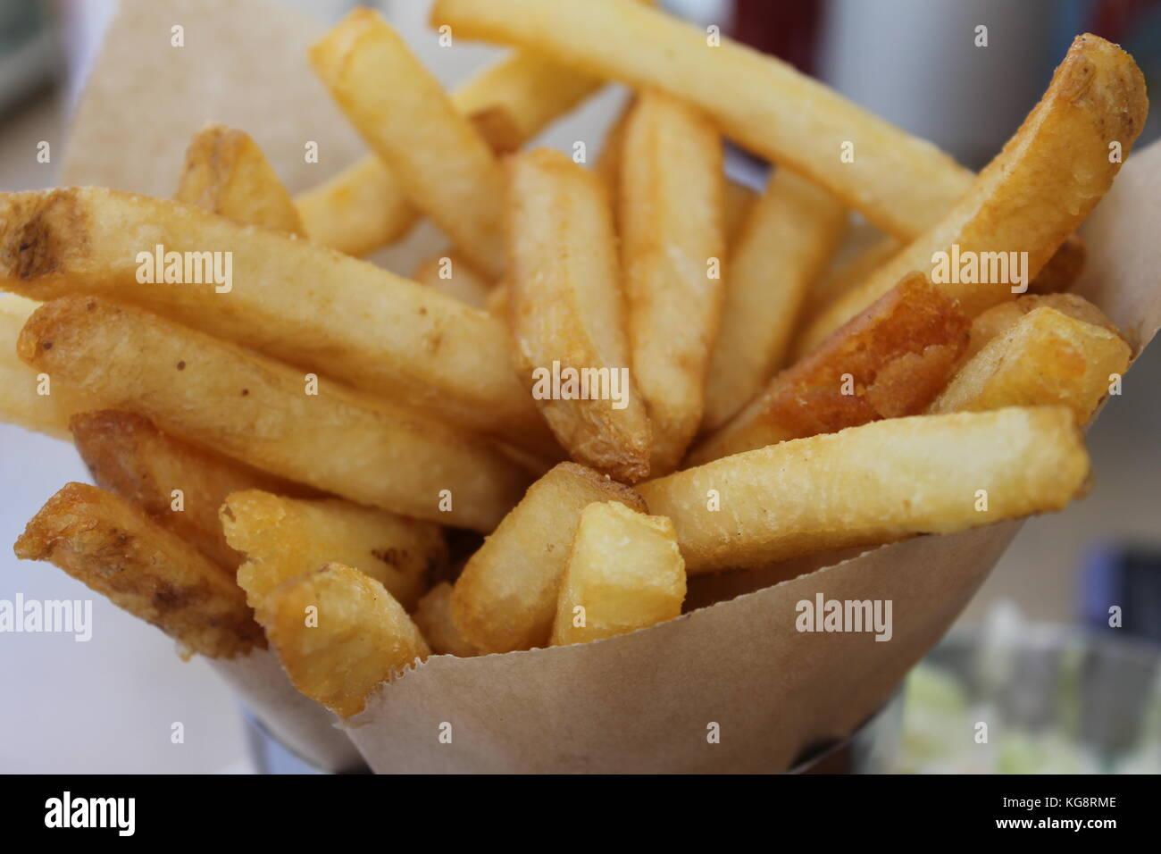 Patatas fritas recién cortadas en un cono de papel marrón Foto de stock