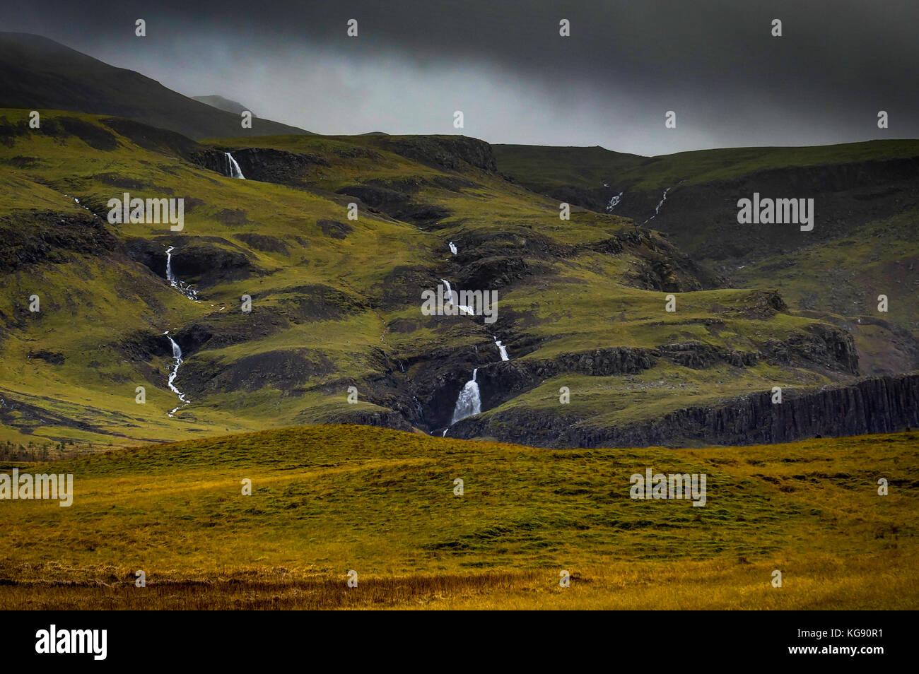 Paisaje islandés con niebla y pequeñas cascadas, montañas con Imagen De Stock