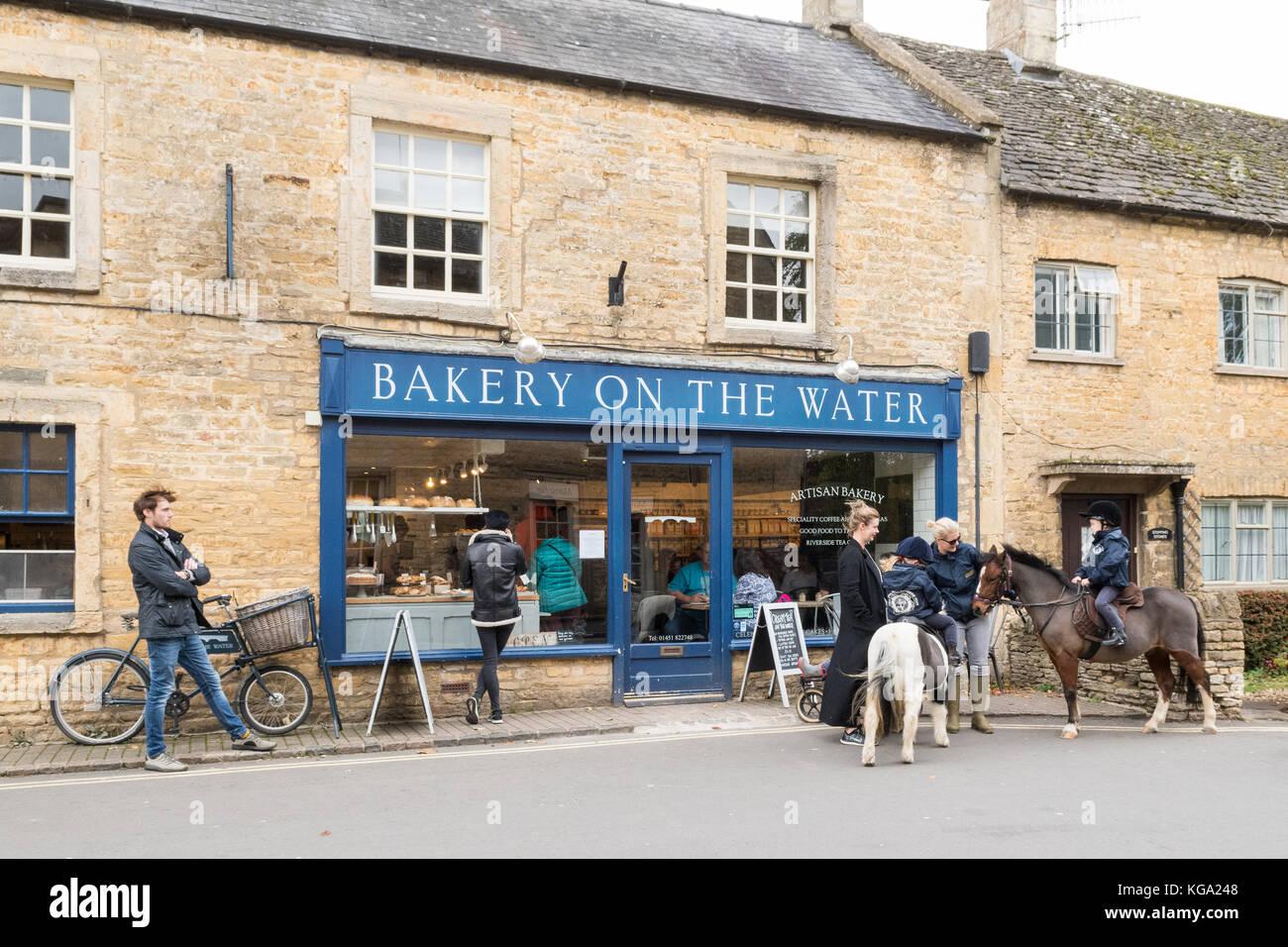 Bourton sobre el agua, Gloucestershire, Inglaterra, Reino Unido - la infancia en ponis fuera artesano de panadería Imagen De Stock