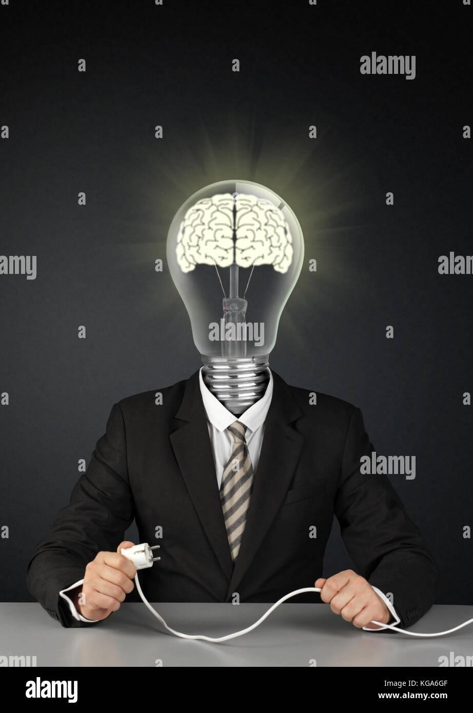 Empresario con cabeza de bombilla de luz y enchufe, interruptor cerebro creativo concepto sobre negro Imagen De Stock
