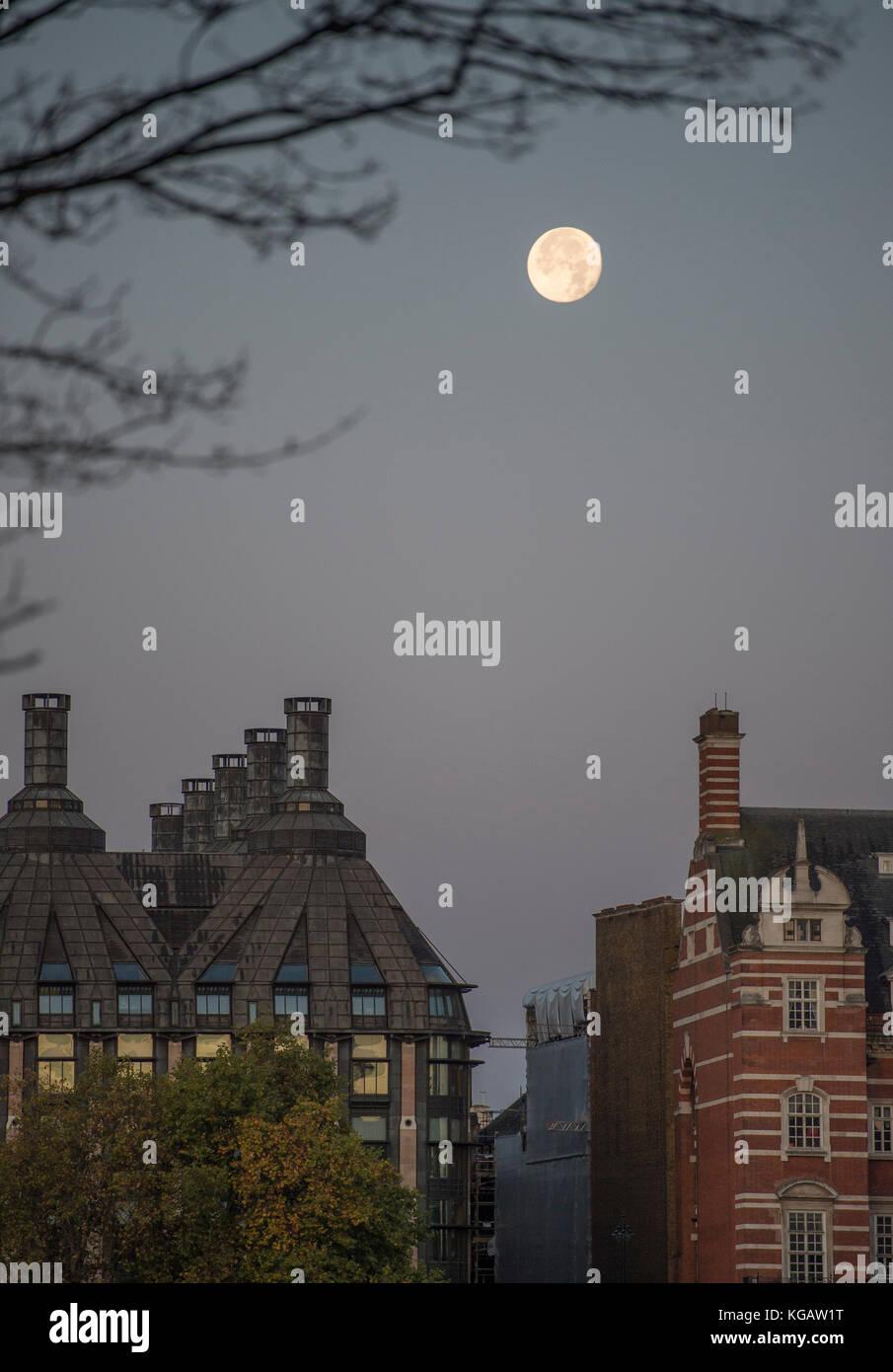 La luna sobre Portcullis House y Old Scotland Yard en amanecer en otoño Foto de stock