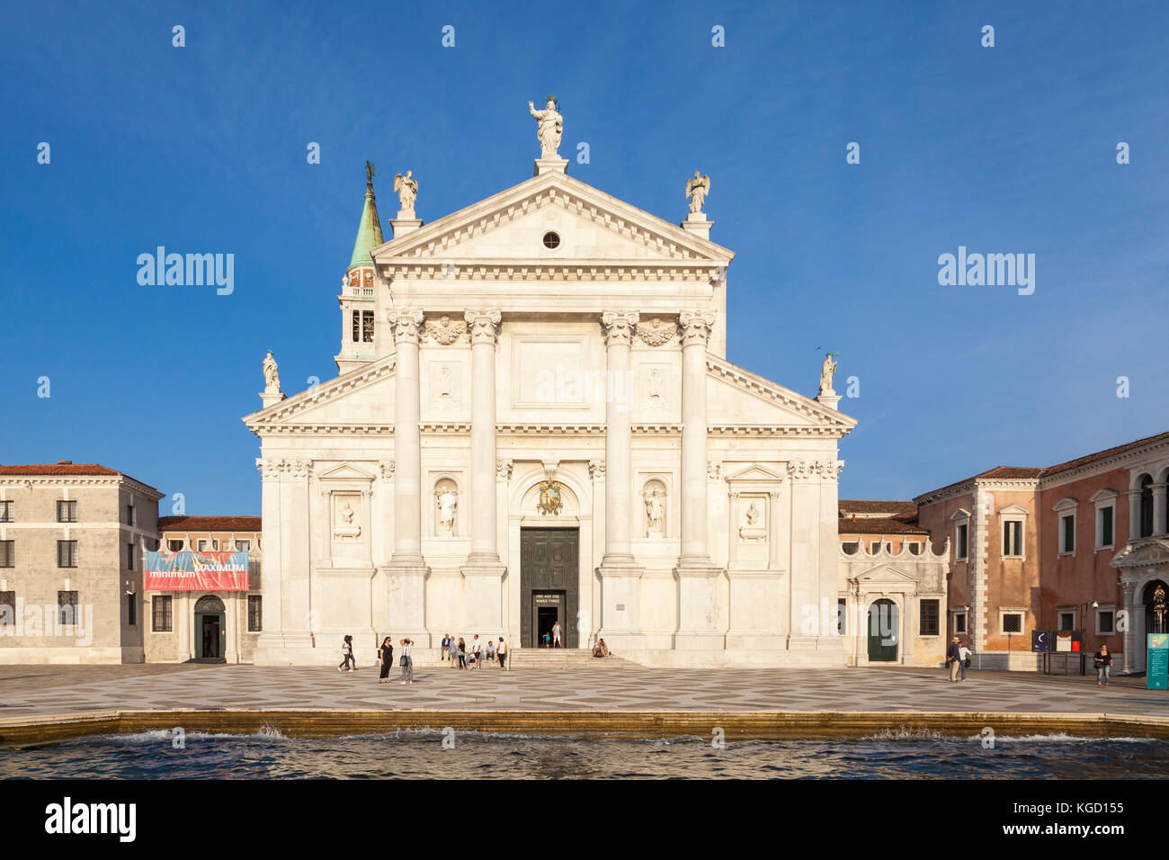 Fachada de la iglesia de San Giorgio Maggiore, diseñada por Palladio en Isola San Giorgio Maggiore, Venecia, Italia al atardecer. Los turistas en la explanada Foto de stock