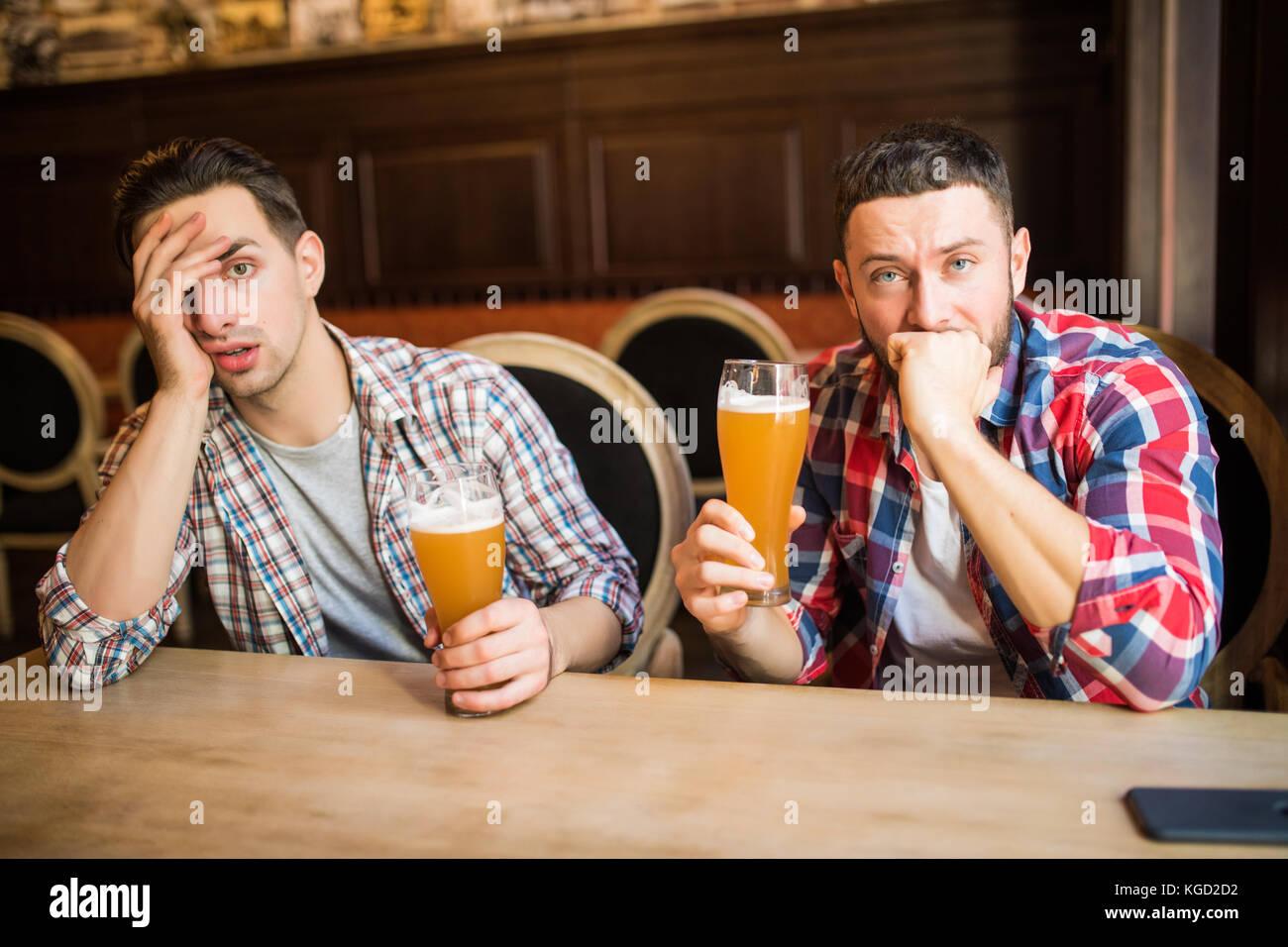 Joven barbudo hombre mirando disgustado y triste tener cerveza en el pub copyspace depresión estrés cansado Imagen De Stock