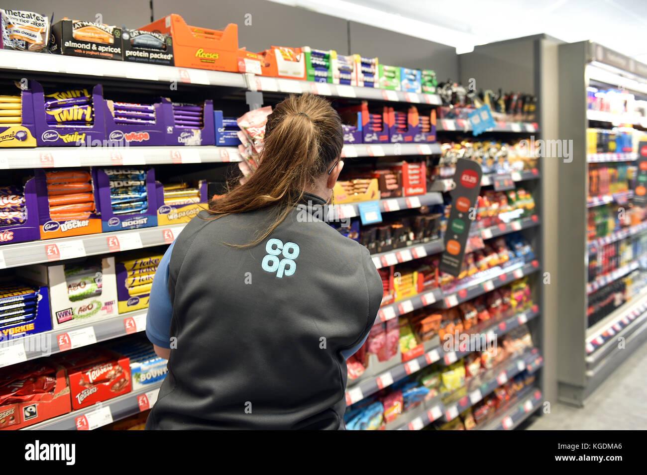 Apilamiento de estante en una tienda de alimentos cooperativos, vista posterior de un miembro del personal de chocolate Imagen De Stock