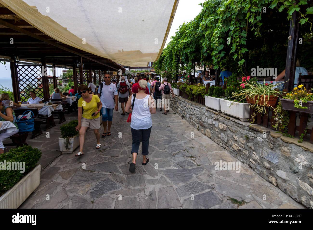 Calle y turistas, restaurantes típicos y cafés en la ciudad patrimonio mundial de la Unesco de Nesebar. Bulgaria. Foto de stock
