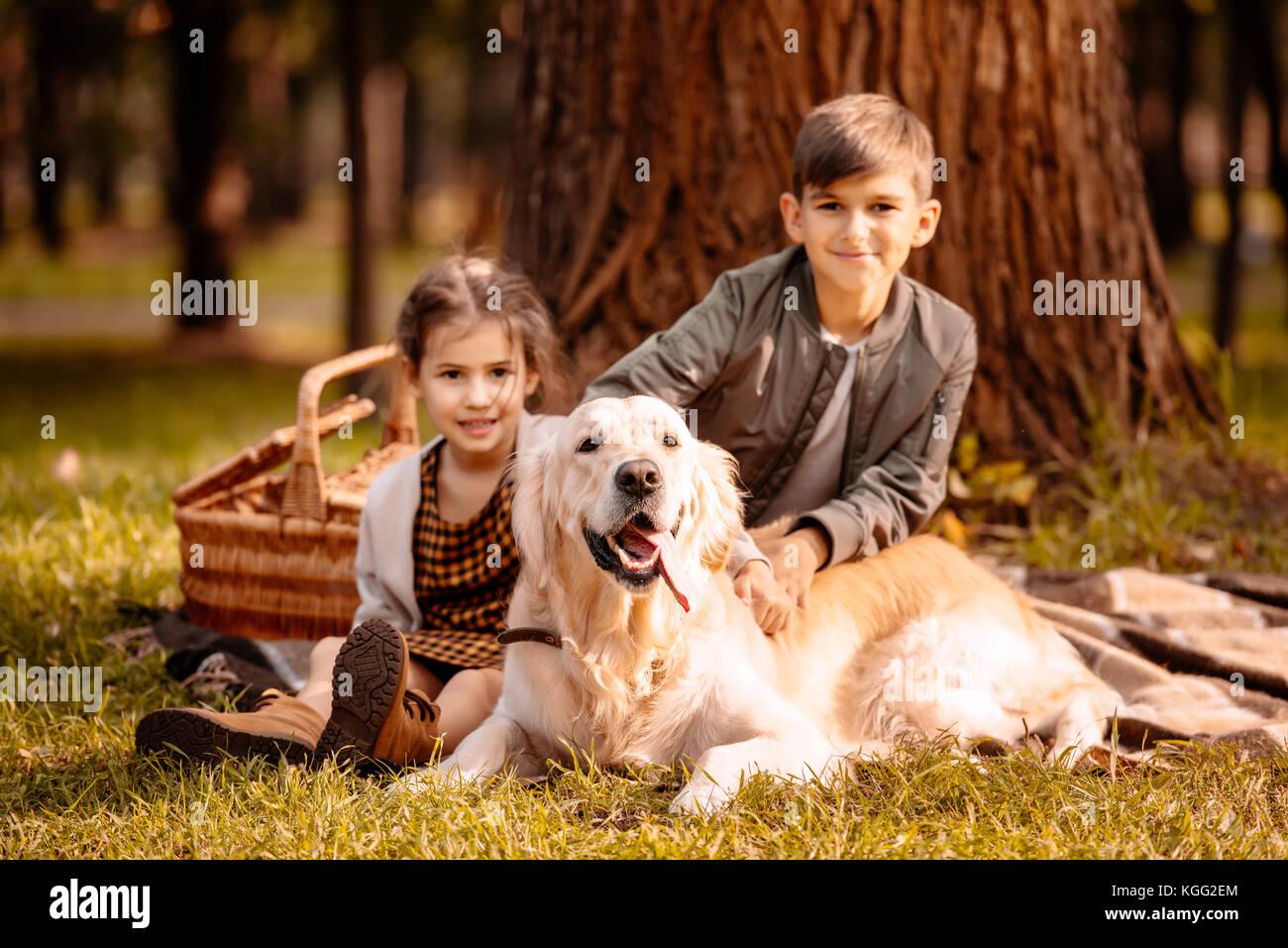 Niños acariciándole perro en park Imagen De Stock
