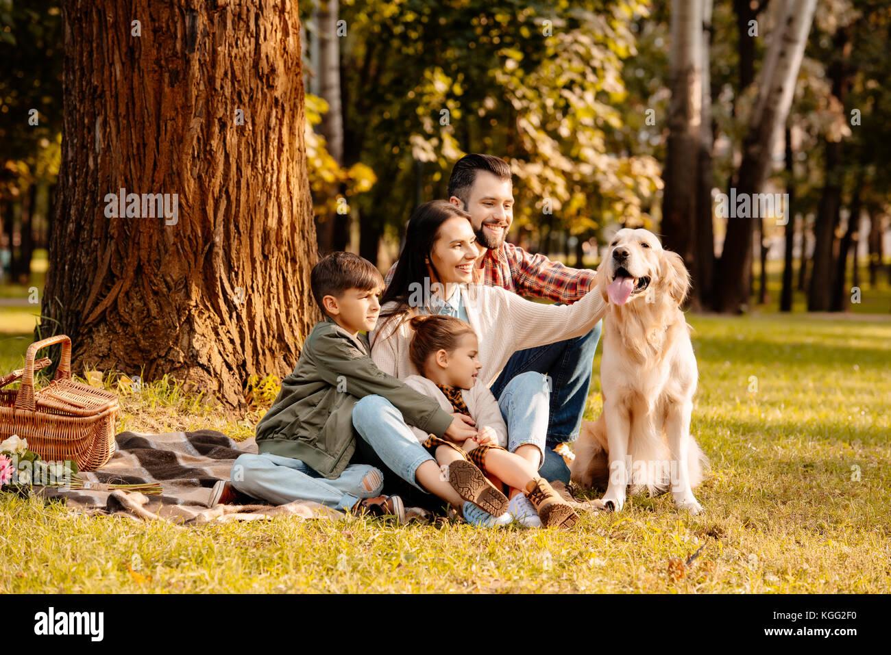 Picnic en familia acariciándole perro Imagen De Stock