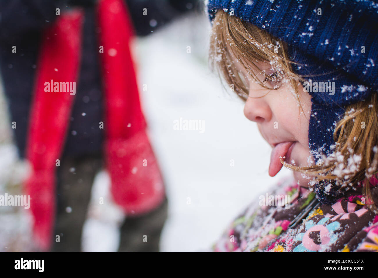 Un niño está fuera vistiendo ropa de invierno con nieve alrededor de ella. Foto de stock