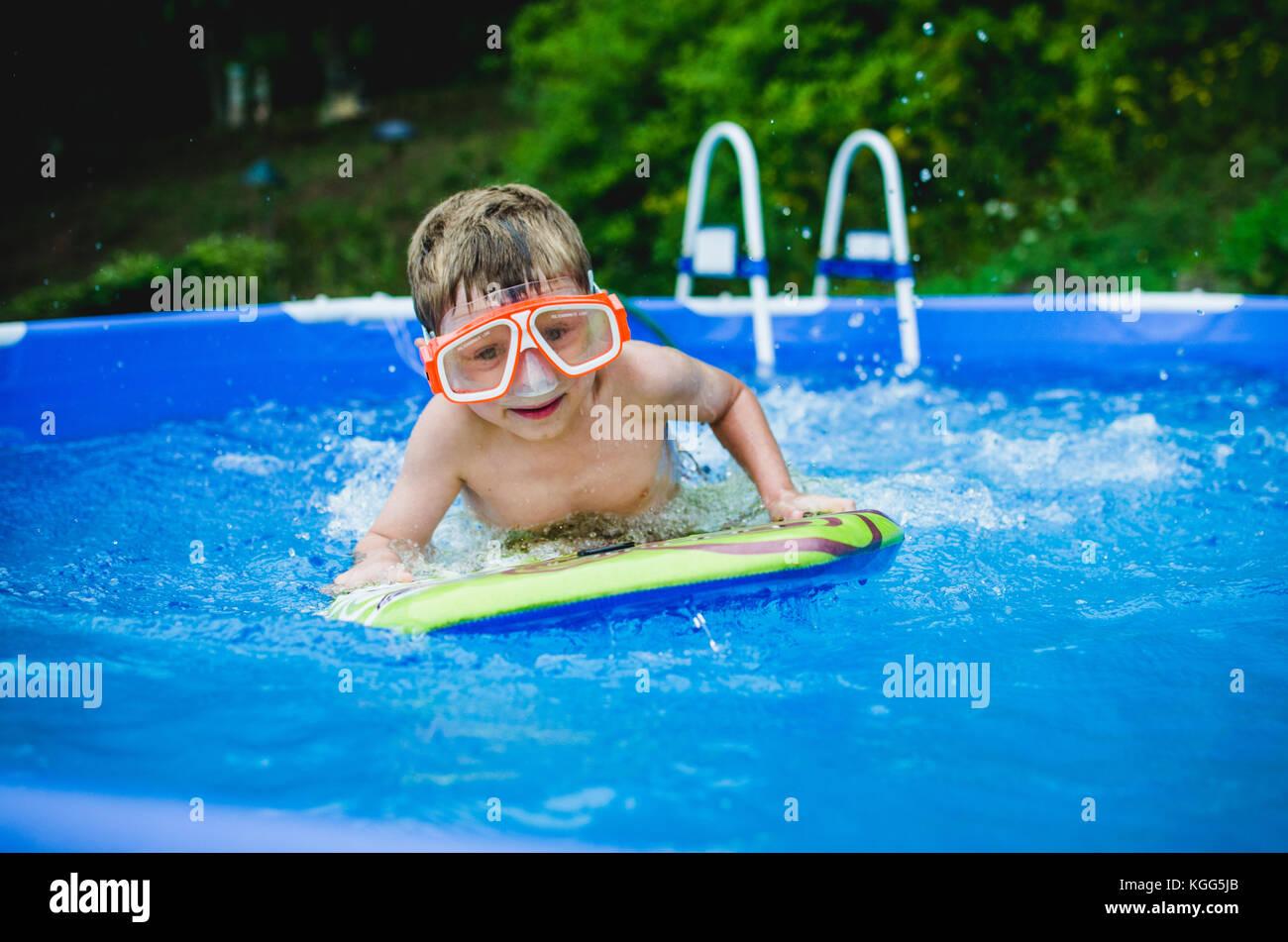 8-9 años jugando en un boogie board en una piscina en verano. Imagen De Stock