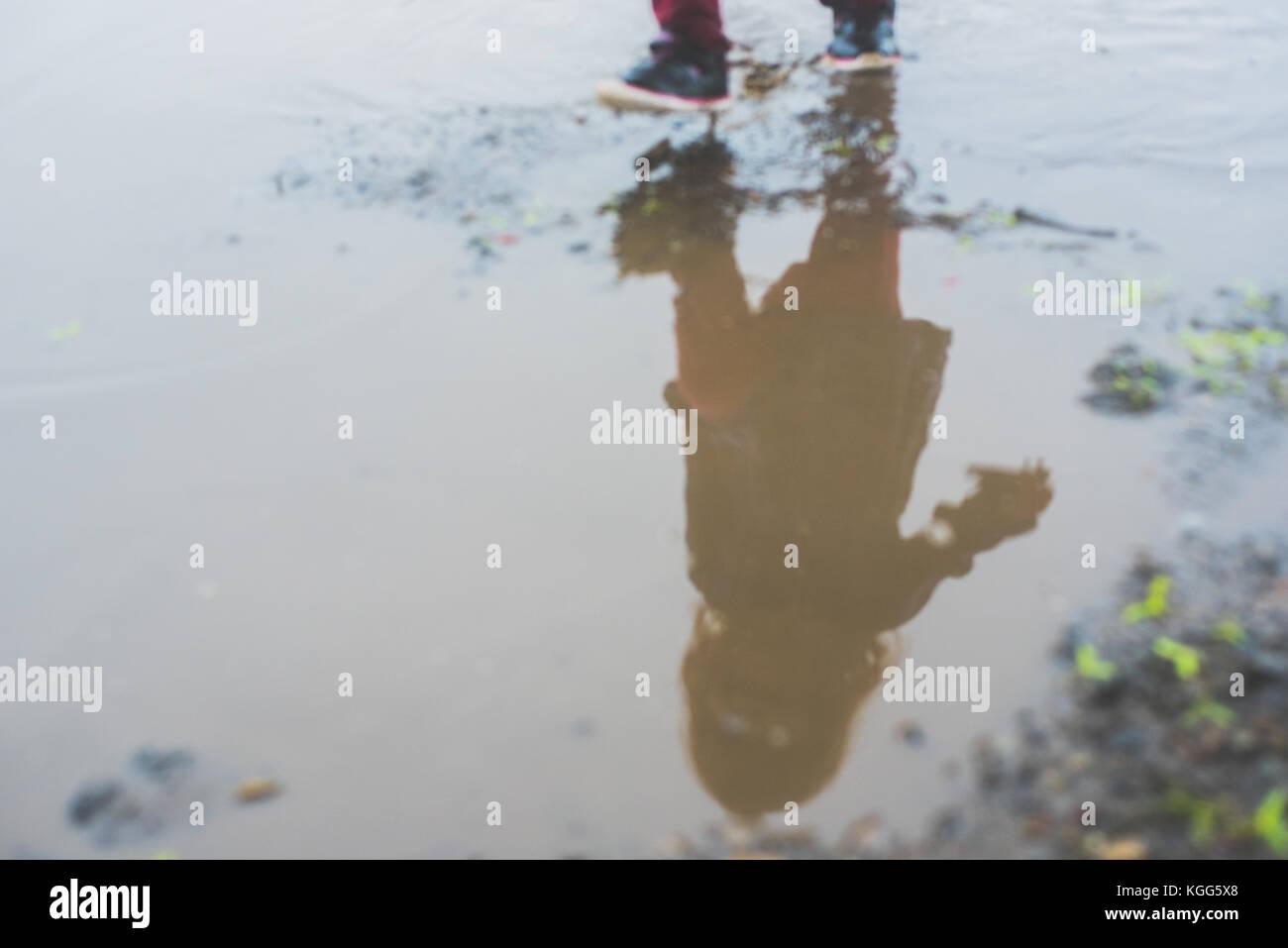 Niño caminando en un charco de lodo Imagen De Stock