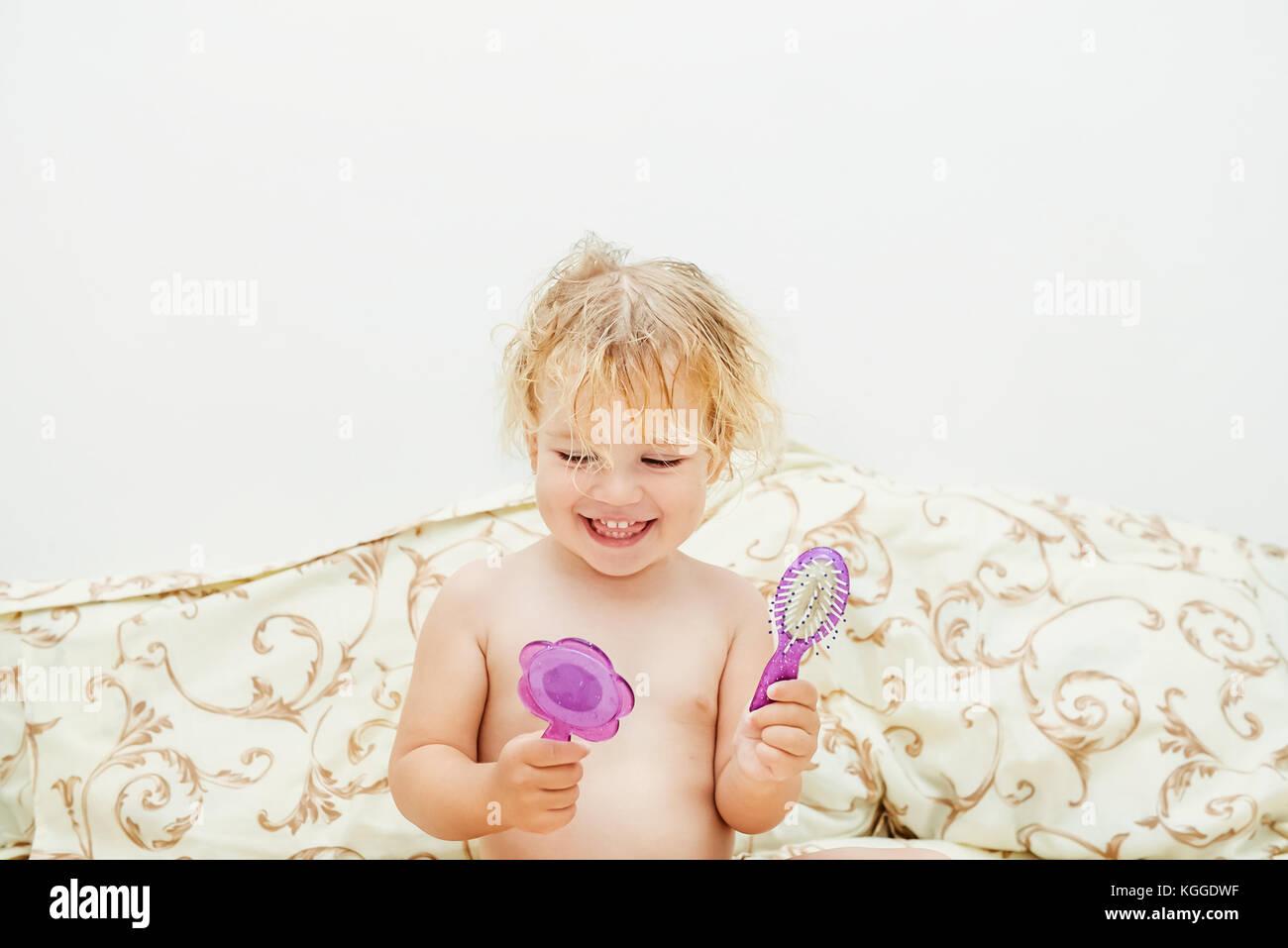 Niña sonriente después de un baño con espejo y peine niño cepillarse el pelo sentada en la cama. Imagen De Stock