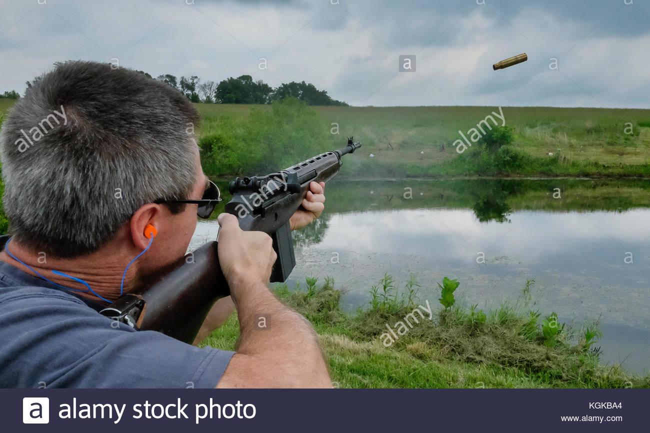 Un hombre que dispara un rifle a objetivos en una granja. Imagen De Stock