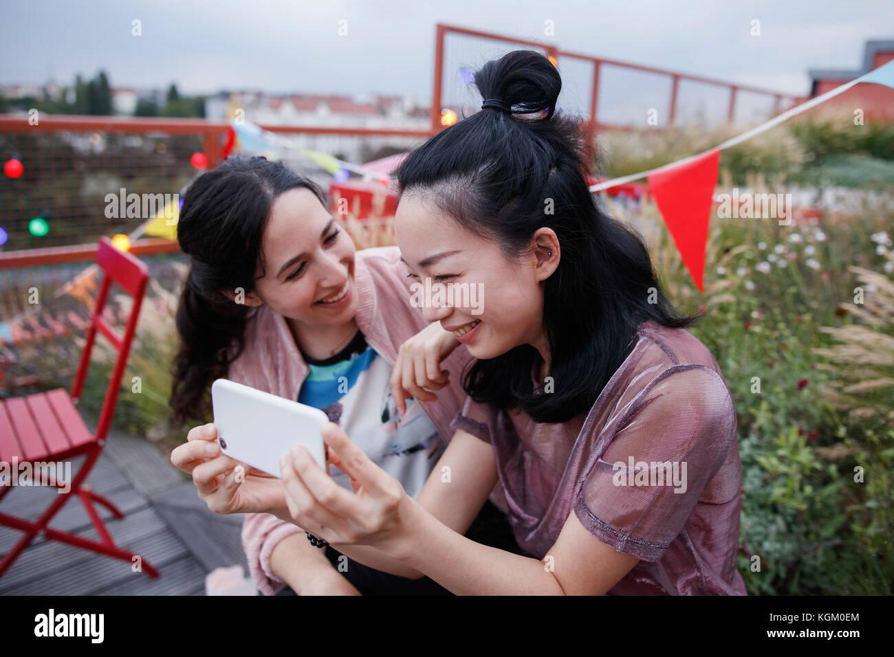 Mujer mirando feliz amiga usando smart phone en el patio Imagen De Stock
