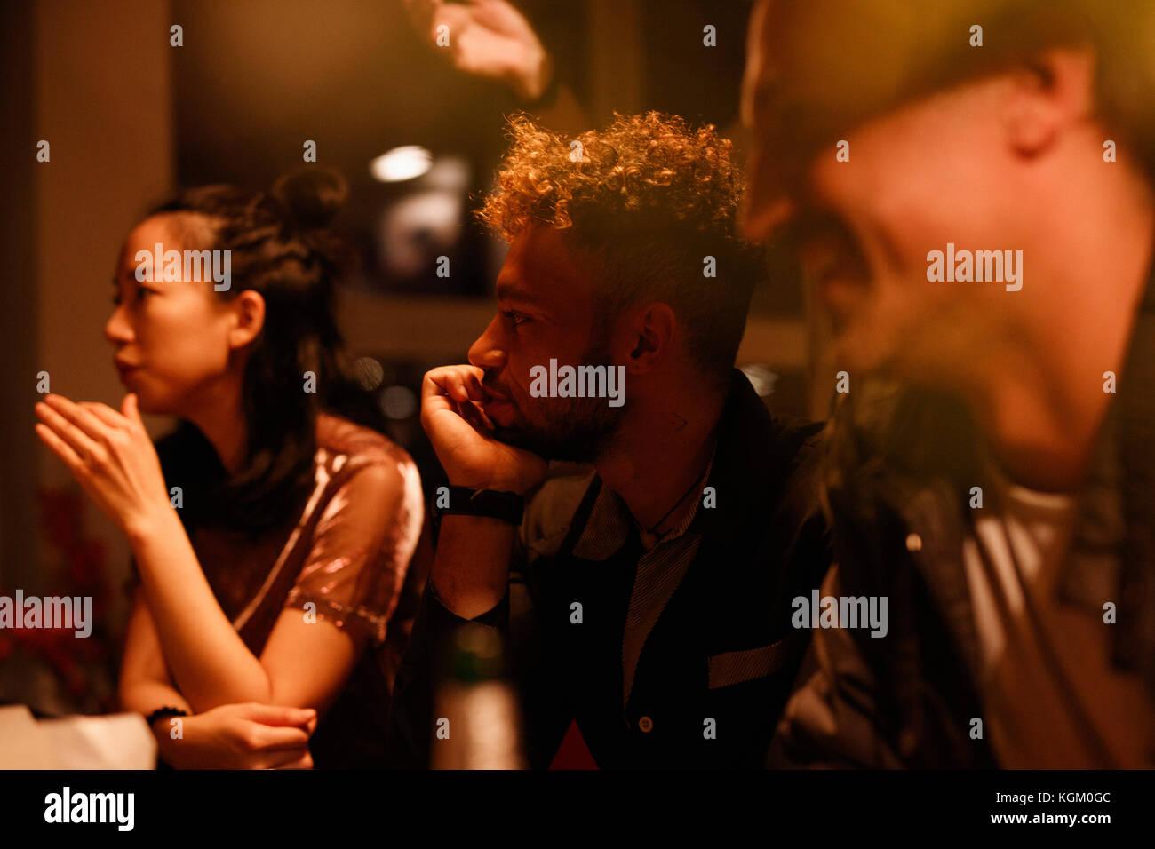 Hablando de amigos masculinos y femeninos durante la fiesta en casa Imagen De Stock