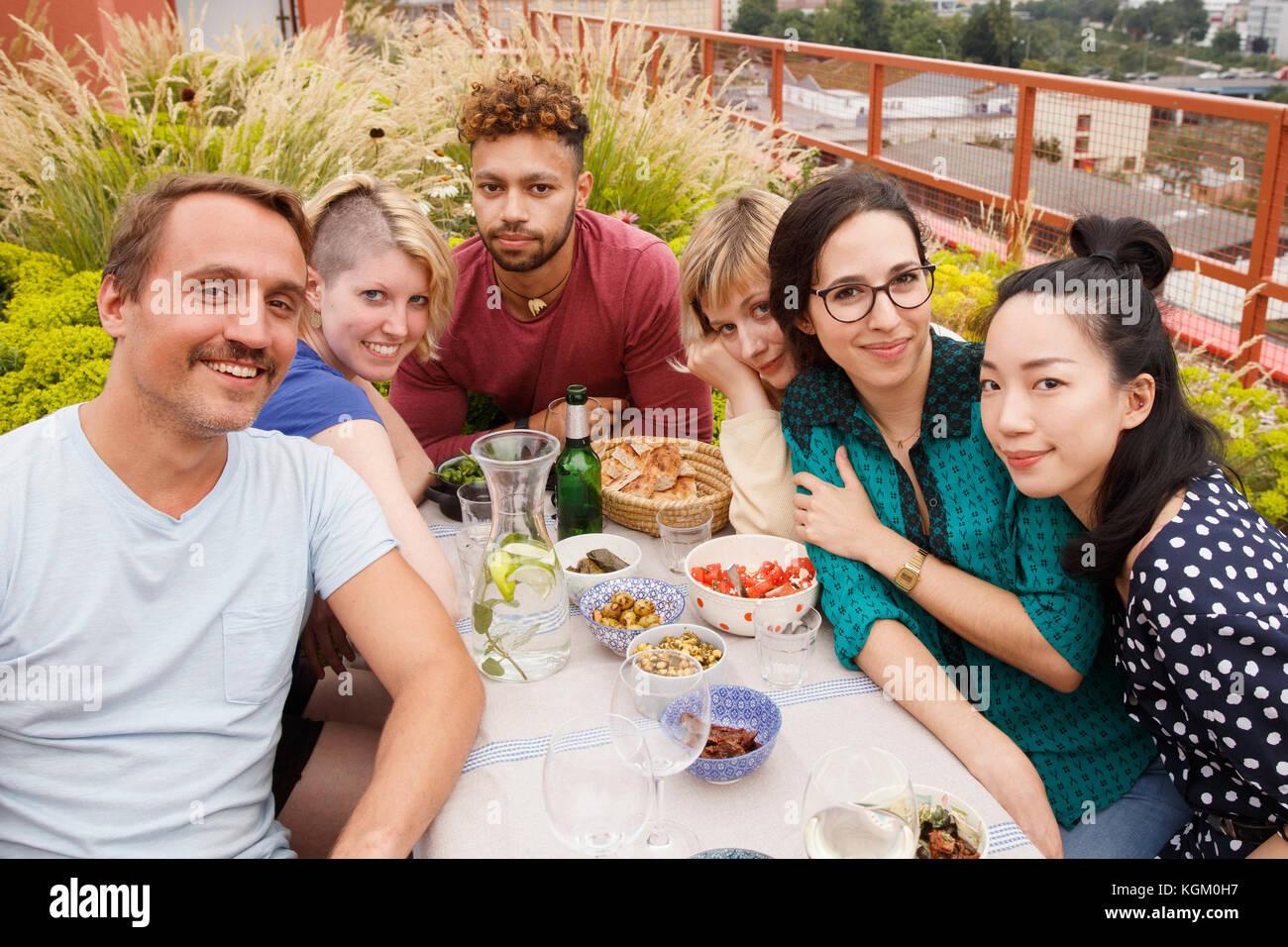 Retrato de macho y hembra feliz amigos sentado en la mesa al aire libre en el patio Imagen De Stock