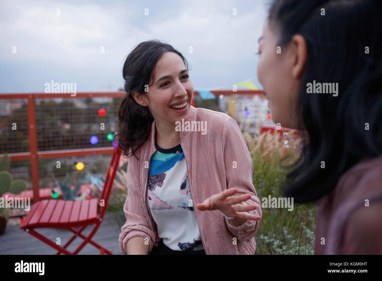 Feliz mujer hablando a una amiga mientras está sentado en el patio Imagen De Stock
